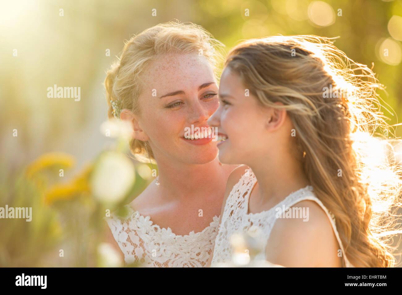Bride talking to Bridesmaid in domestic garden - Stock Image