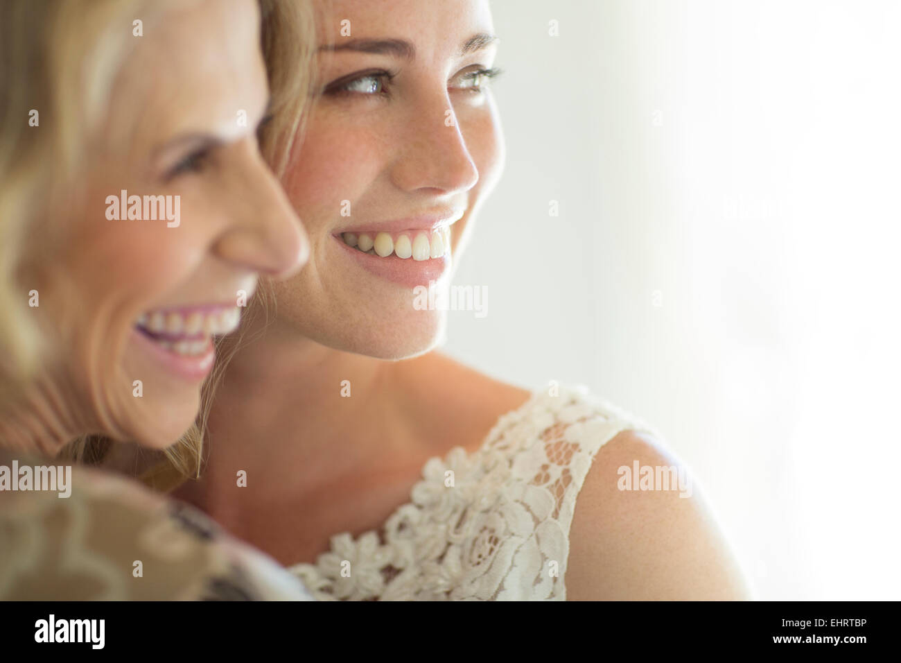 Matron of honor and bride smiling in domestic room - Stock Image