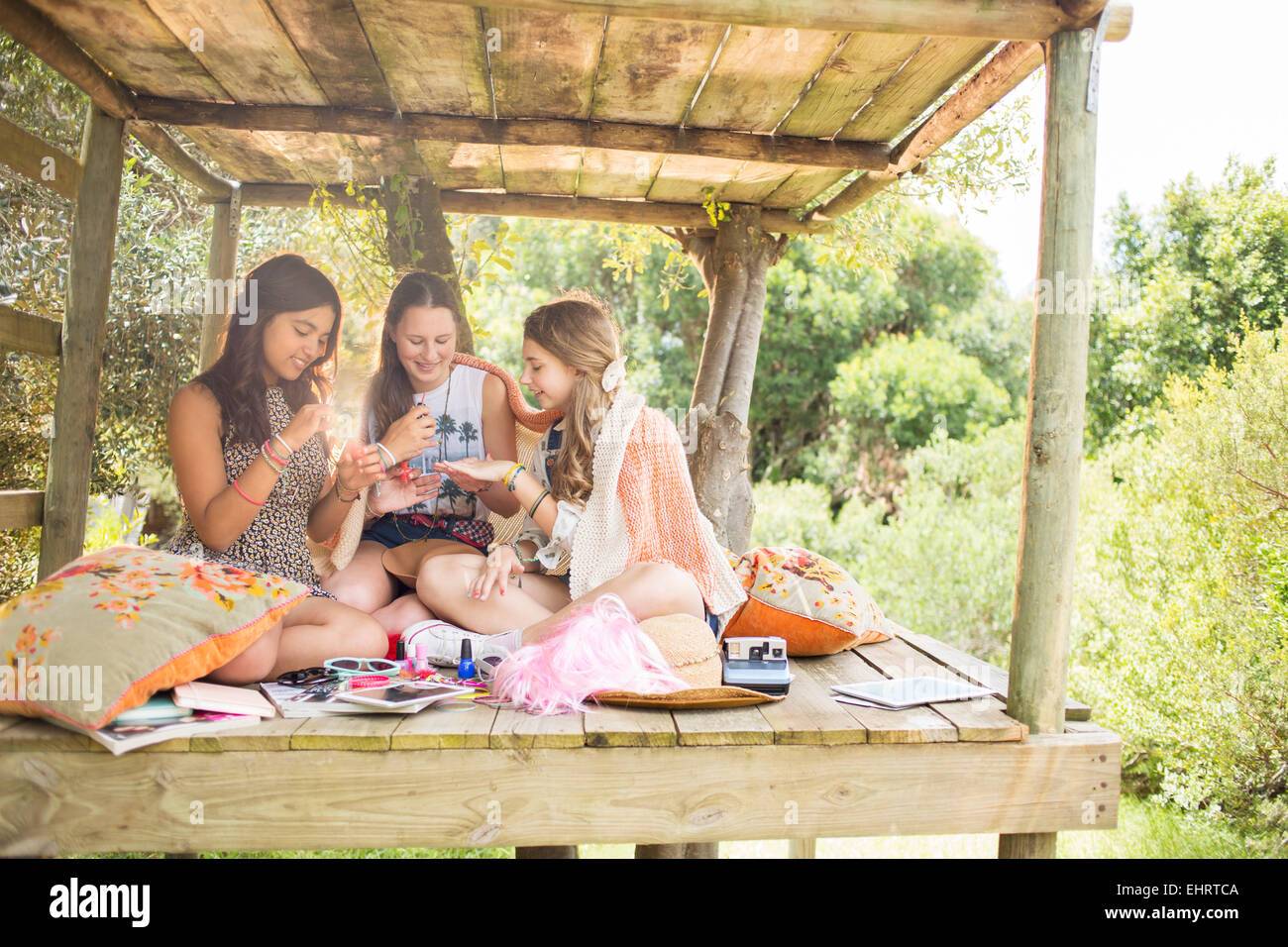Three teenage girls playing in tree house in summer - Stock Image