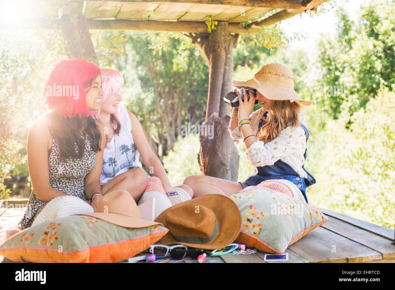 Three teenage girls taking photos in tree house in sunlight - Stock Image
