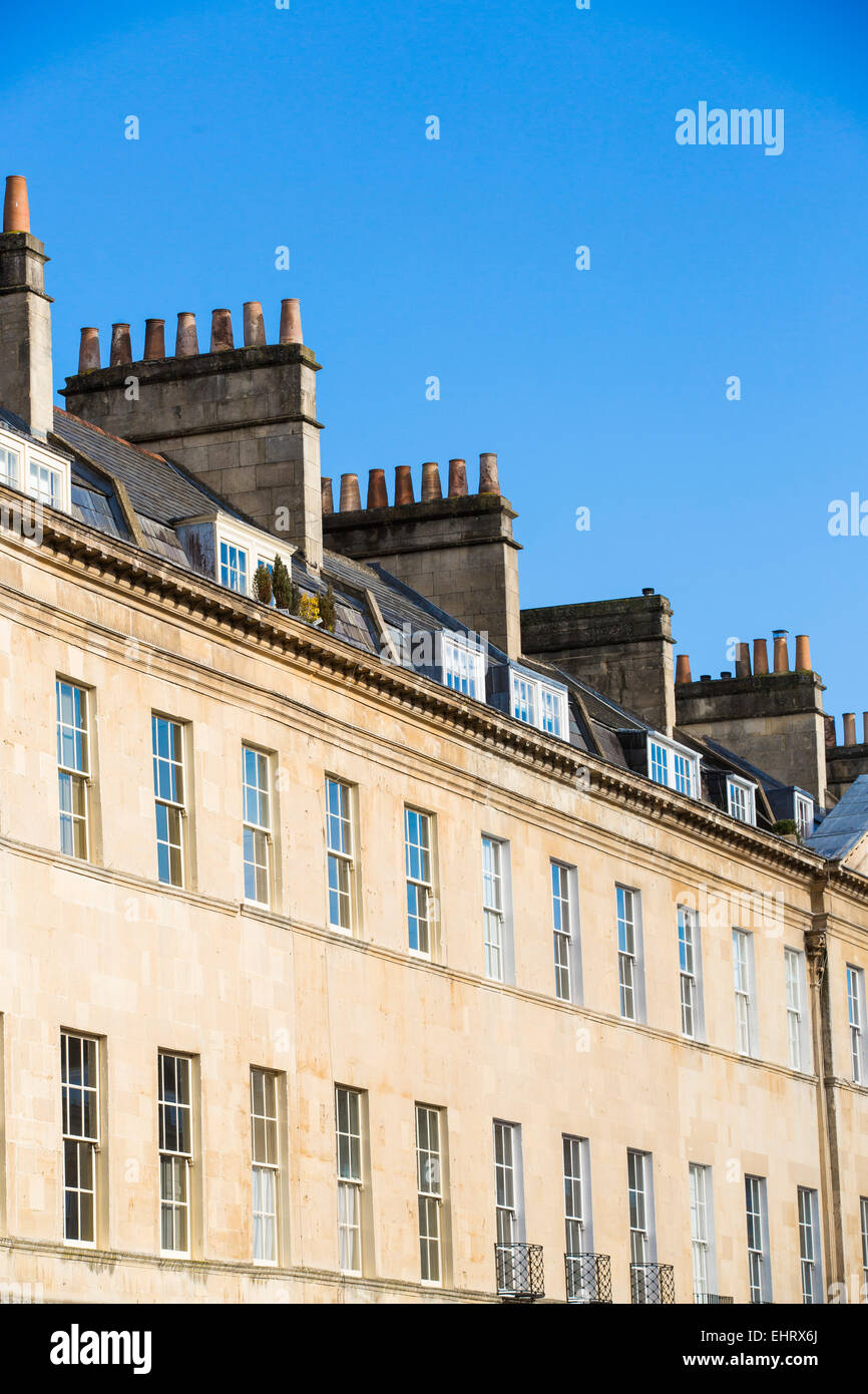 Angled view of terraced Georgian houses in Bath, Somerset, on a sunny day with clear blue sky. - Stock Image