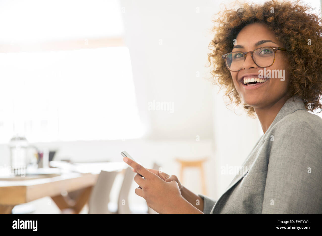 Portrait of smiling office worker with smart phone - Stock Image