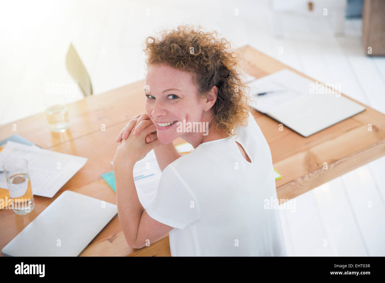 Portrait of young smiling office worker at desk - Stock Image