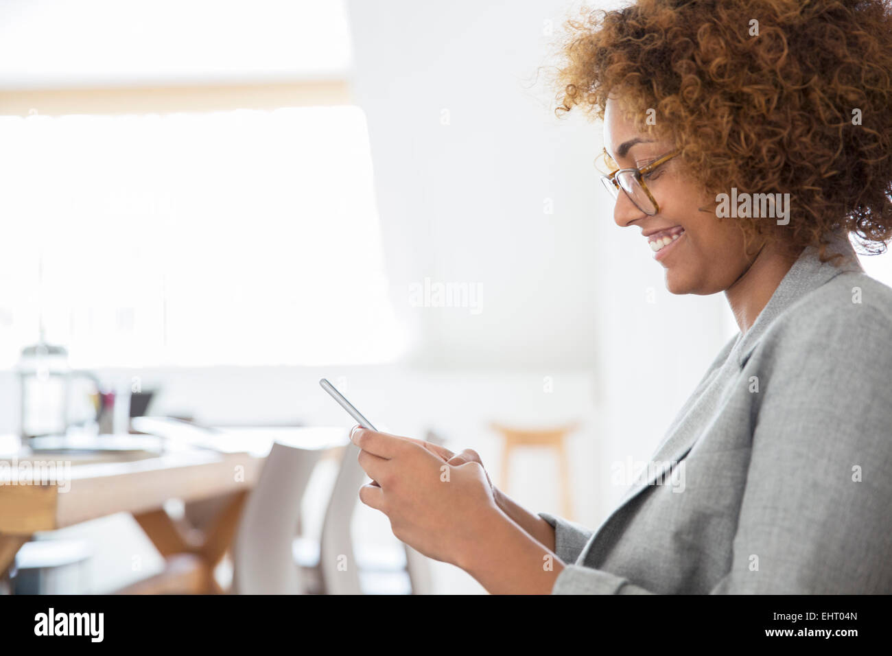 Portrait of woman using smart phone and smiling - Stock Image