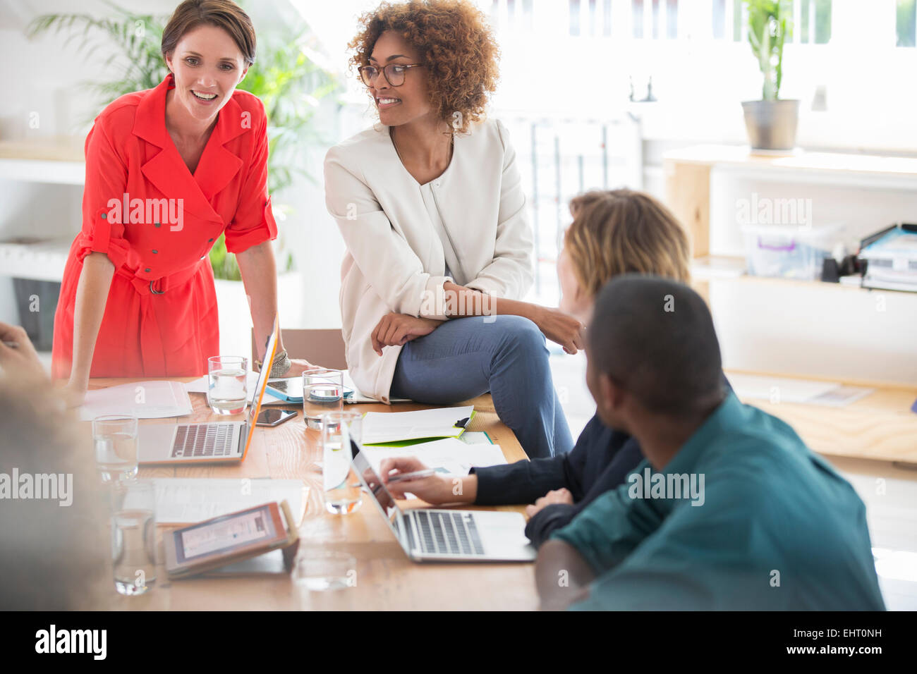 Office workers talking at desk - Stock Image