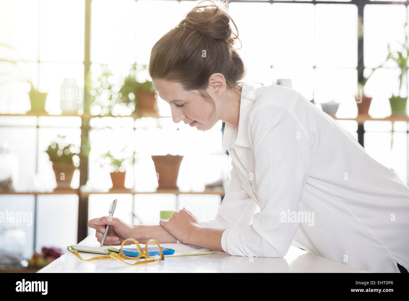 Young woman leaning at desk and writing - Stock Image