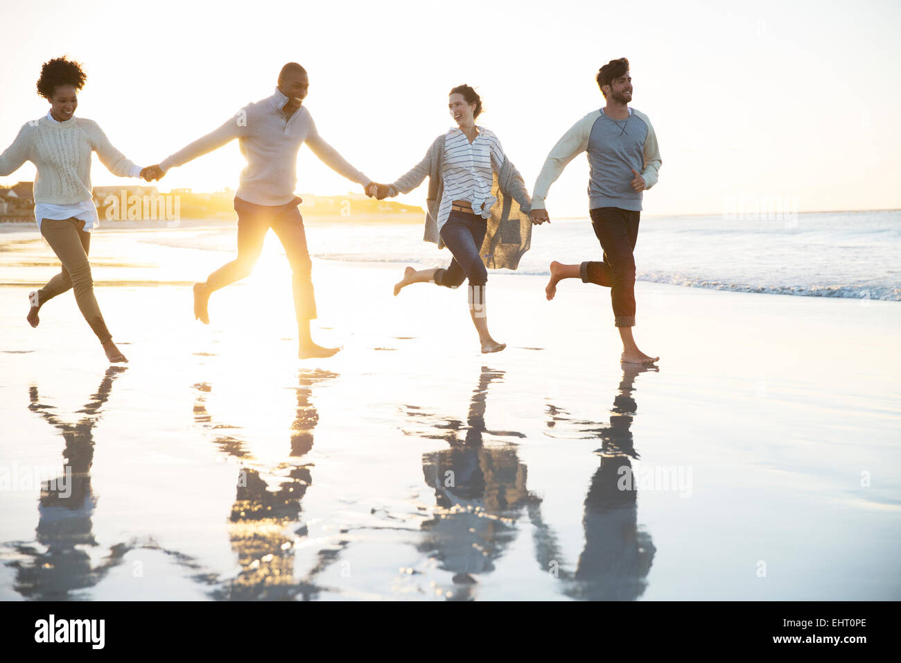 Group of four friends holding hands and running on beach - Stock Image