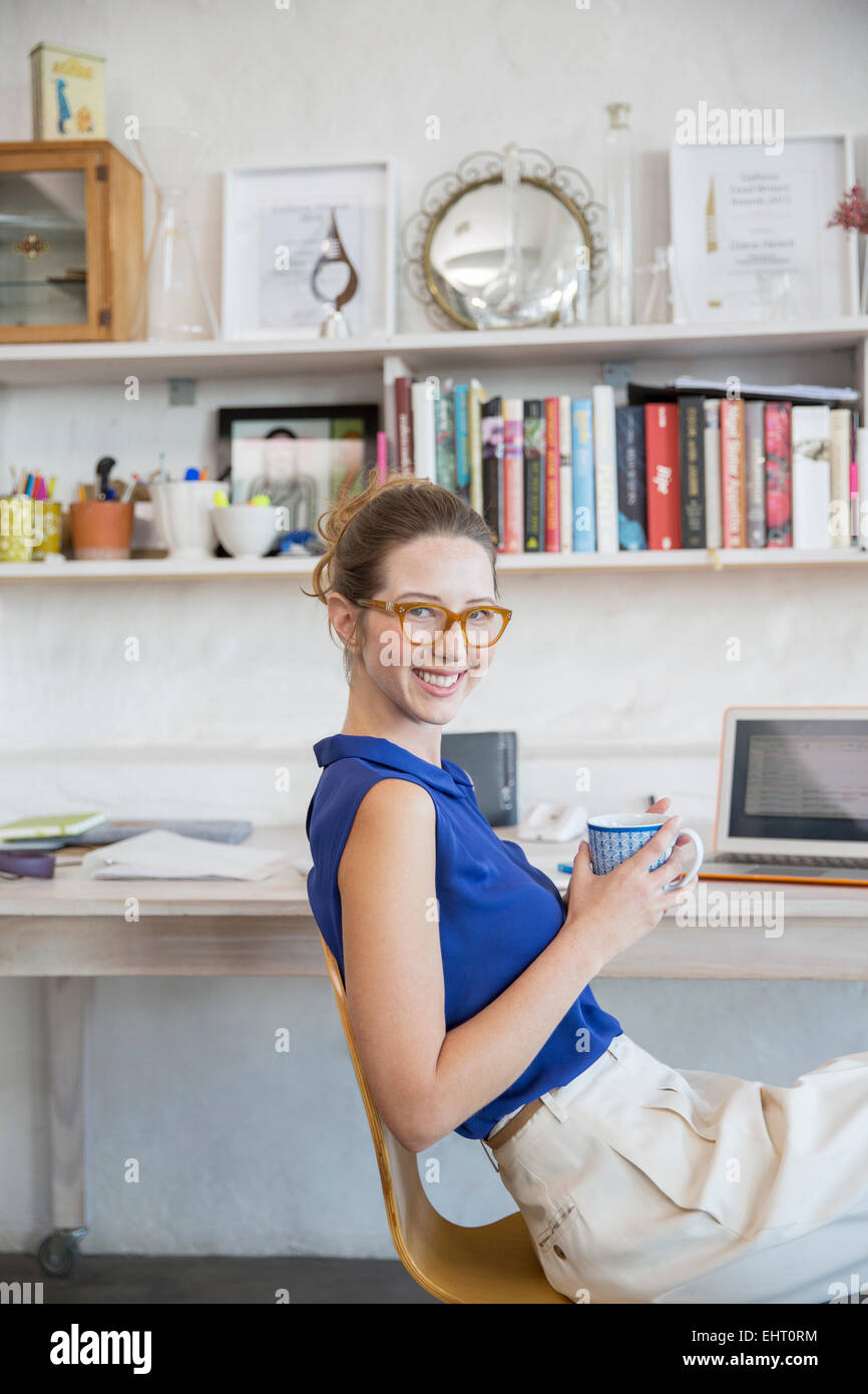 Young woman sitting with mug in home office Stock Photo