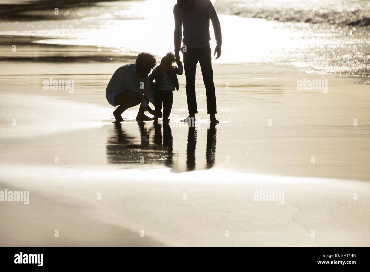 Silhouette of family on beach at sunset - Stock Image