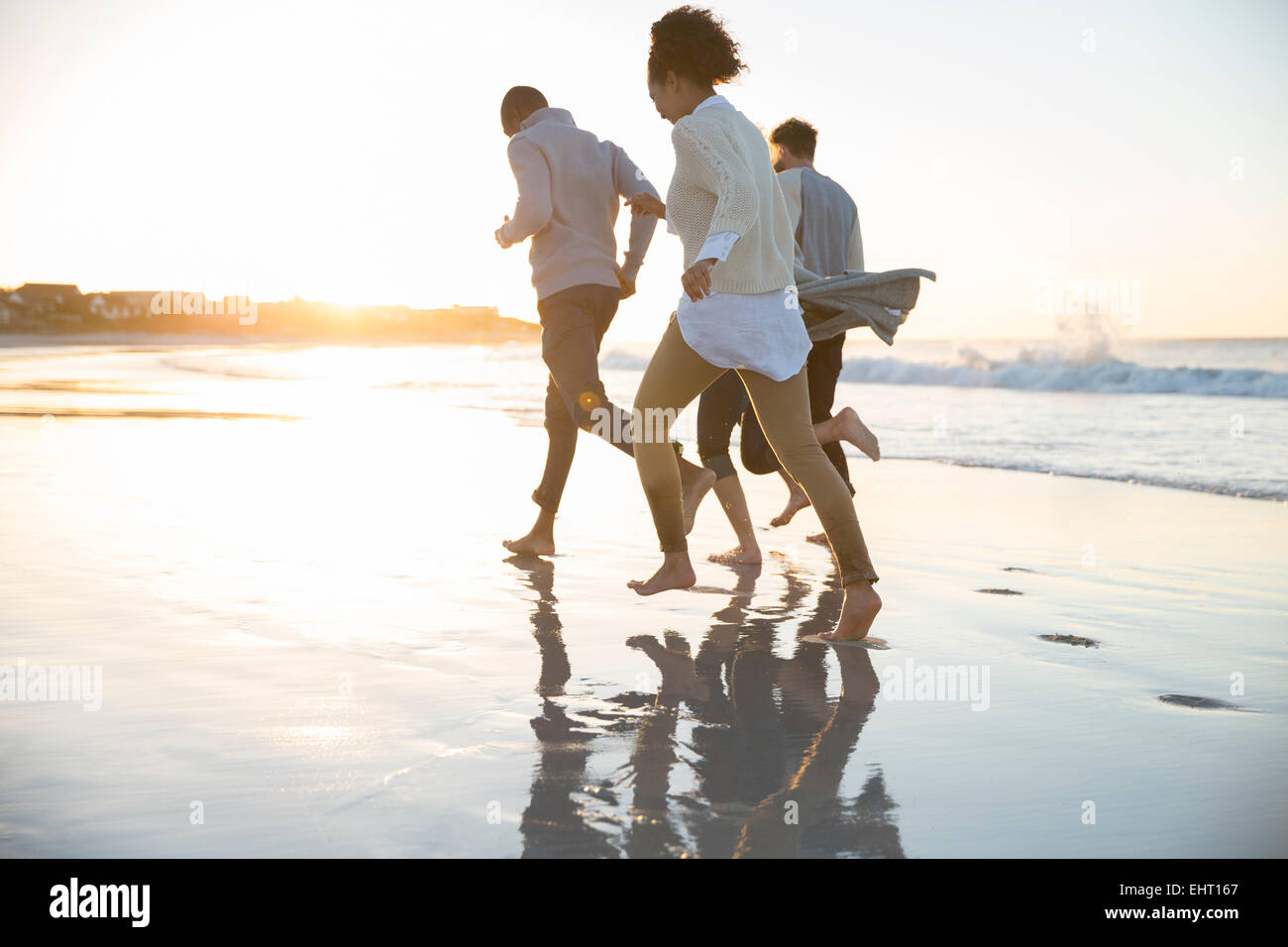 Four friends running ob beach in evening sun - Stock Image