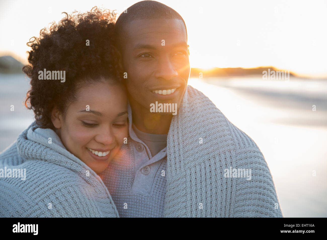 Portrait of couple wrapped in blanket on beach - Stock Image