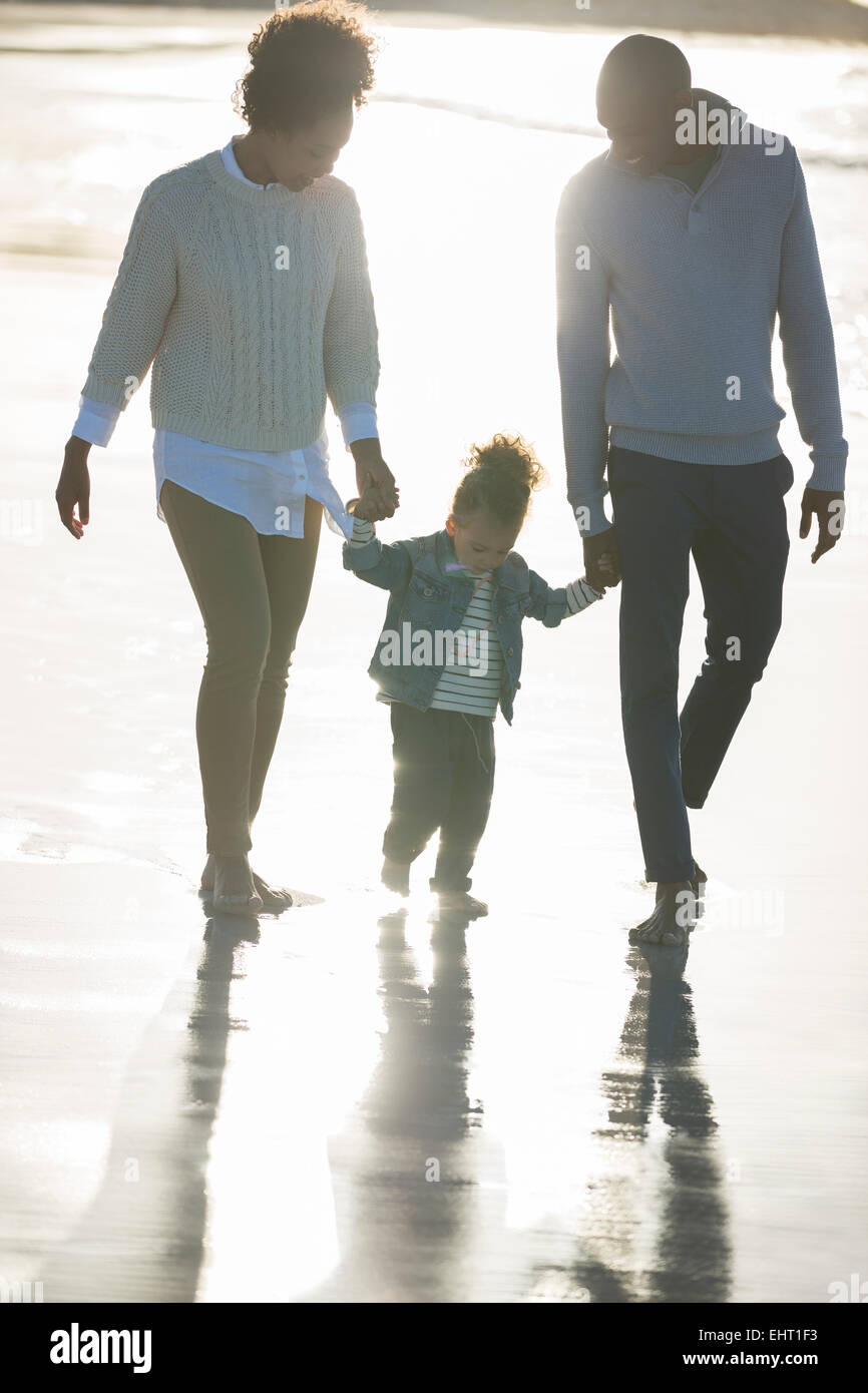 Happy family walking on beach - Stock Image