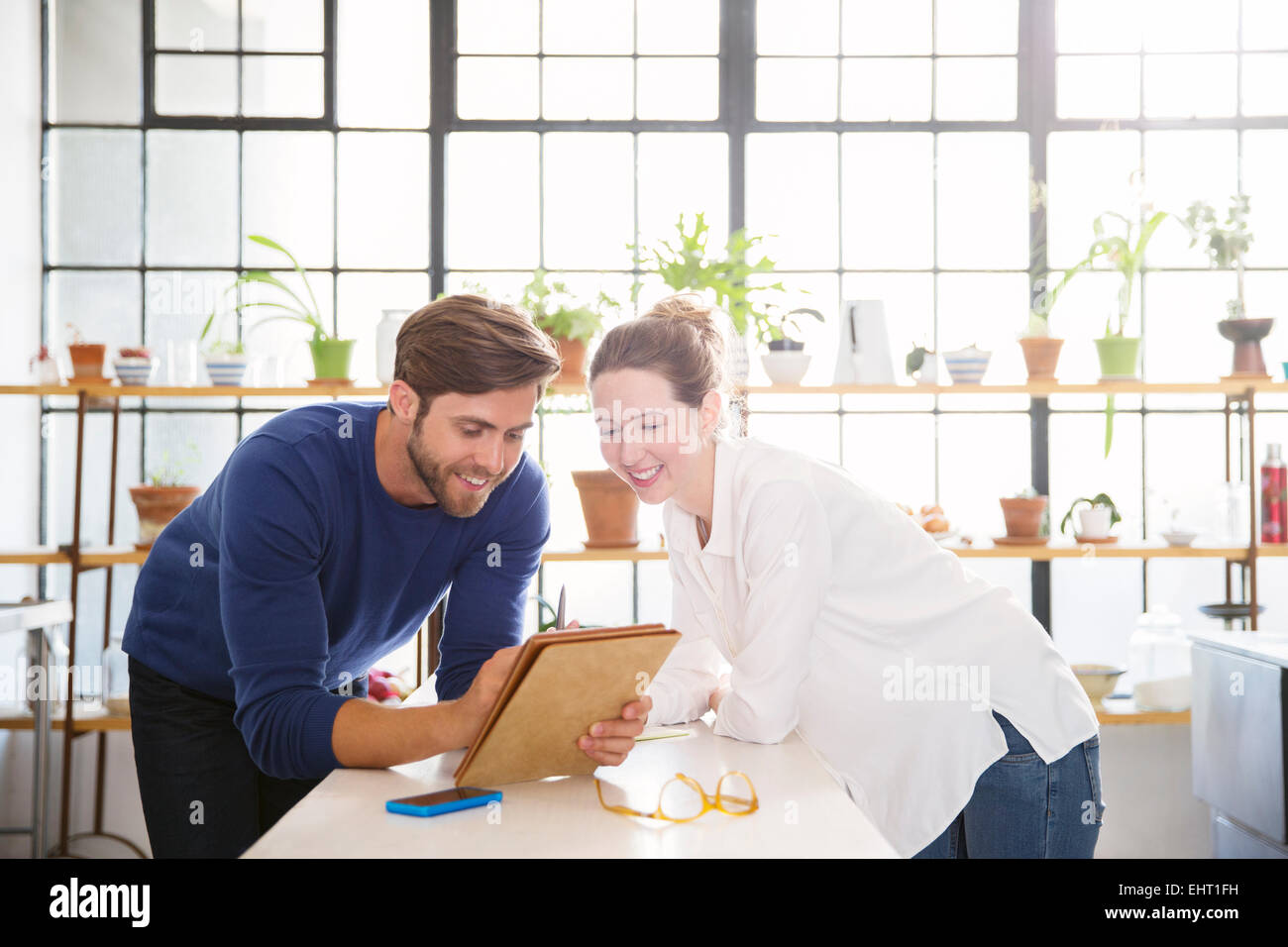 Two young people looking at documents in domestic kitchen - Stock Image