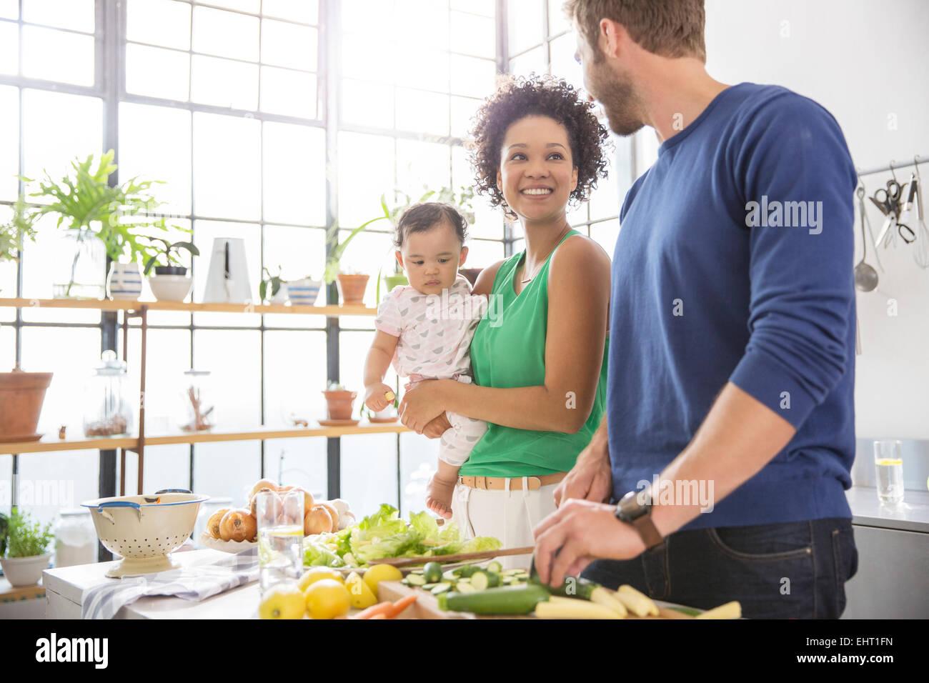 Happy family preparing meal in domestic kitchen - Stock Image
