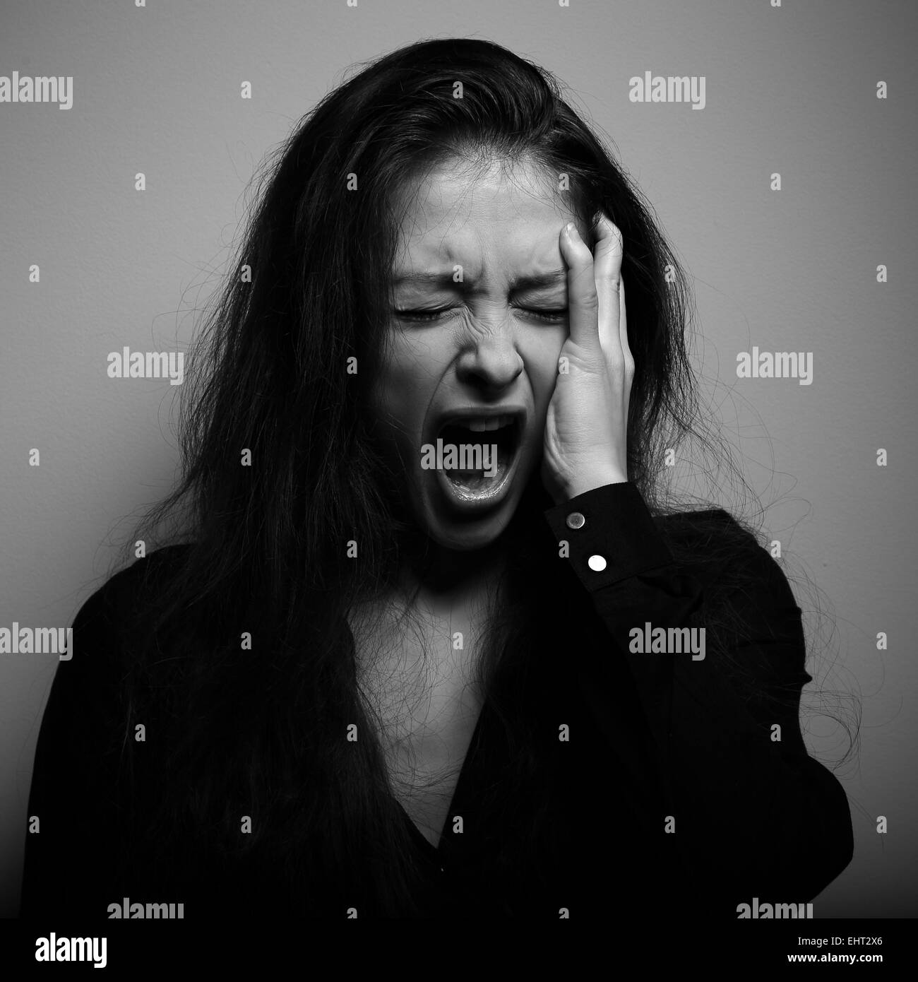 Shouting woman with unhappy, depressed crying face in big grief. Black and white portrait - Stock Image