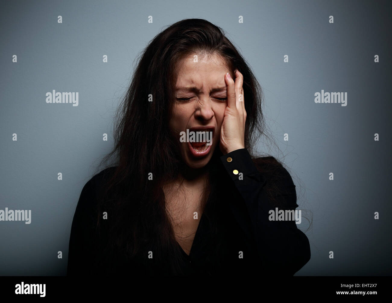Closeup portrait of angry, sad and desperate shouting woman on dark background - Stock Image