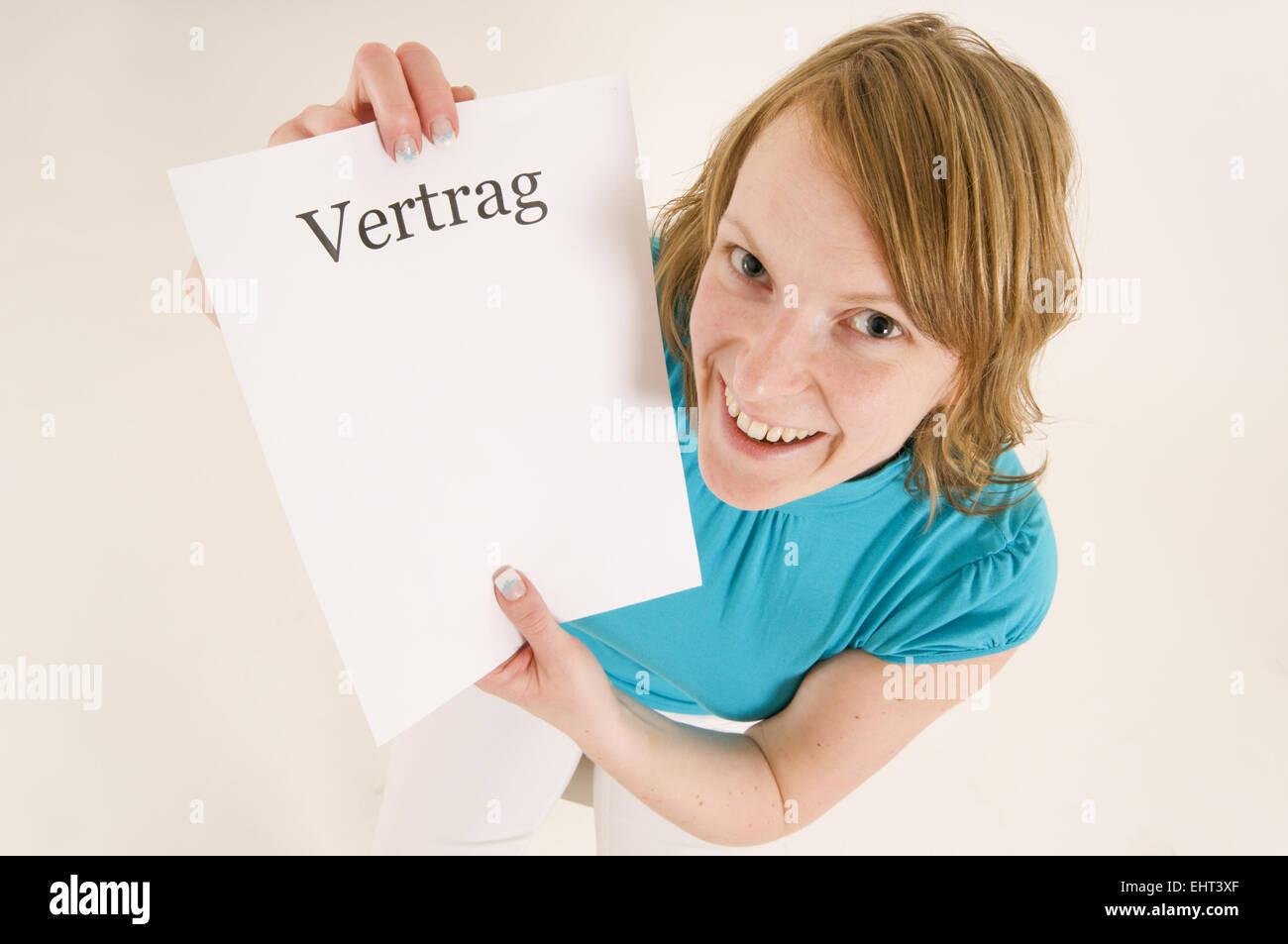 Zufriedene Blonde Frau Hält Einen Blankovertrag In Die Kamera Stock
