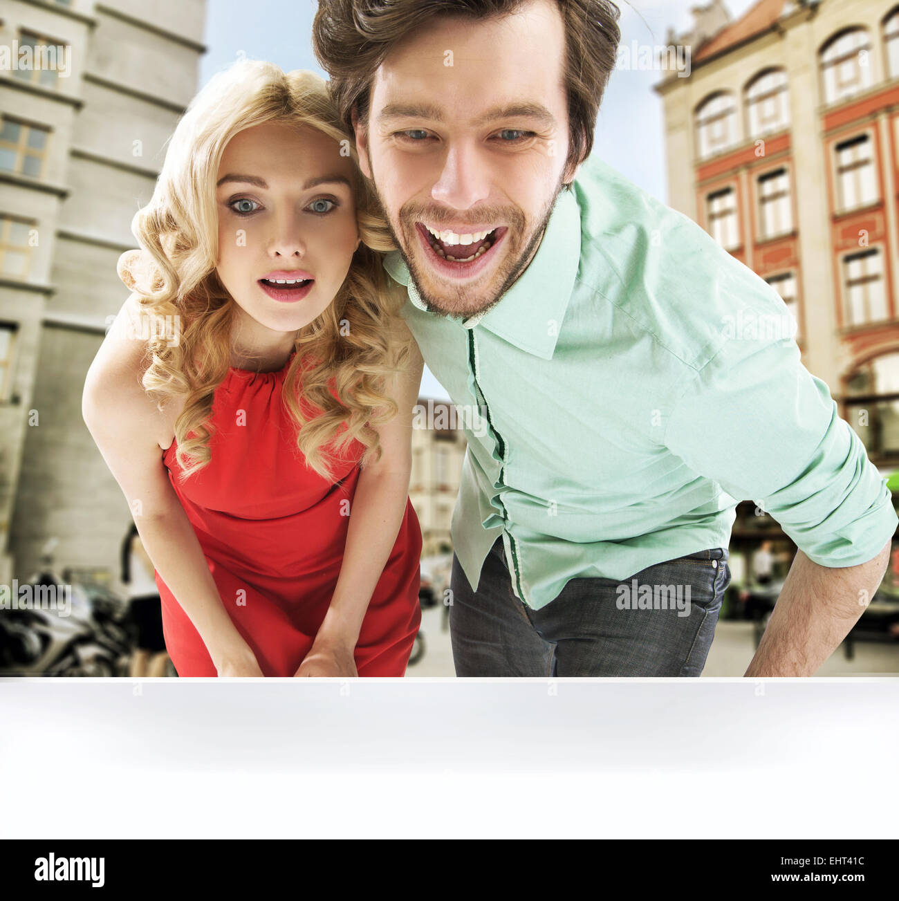 Surprised young couple looking at the shop window - Stock Image