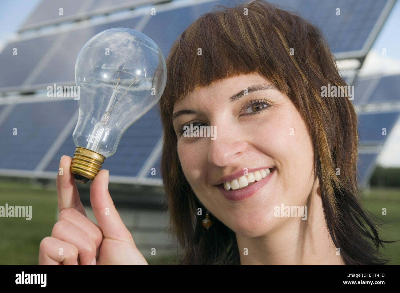 young lady with light bulb - Stock Image