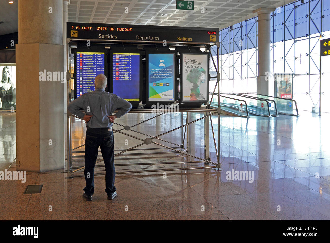 Mature man looking at departures board at Barcelona El Prat ...