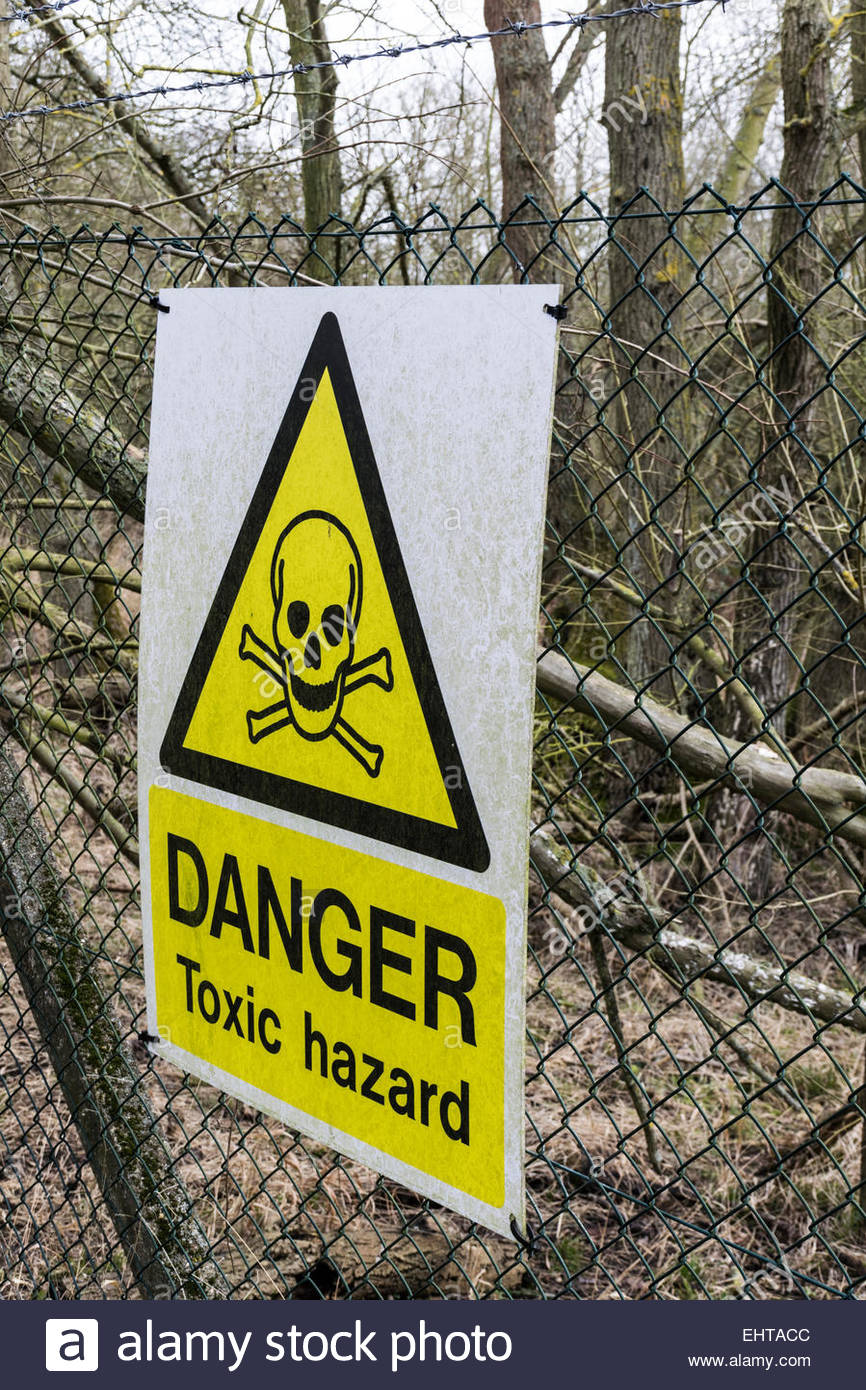 Danger, Toxic hazard, signs on a concrete post and wire fence, with rows of barbed wire at the top - Stock Image