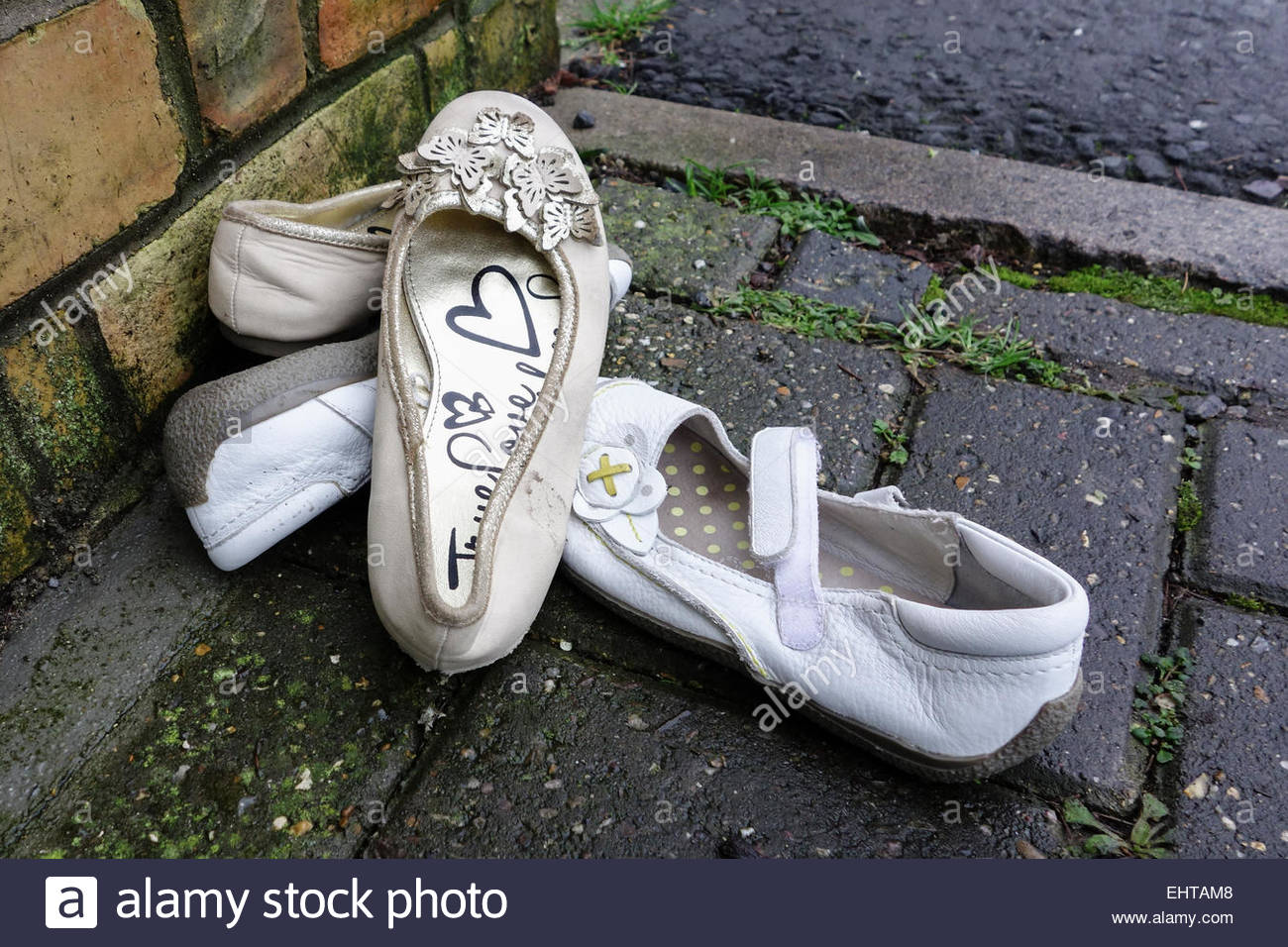 Two pairs of discarded womens shoes on a wet pavement - Stock Image