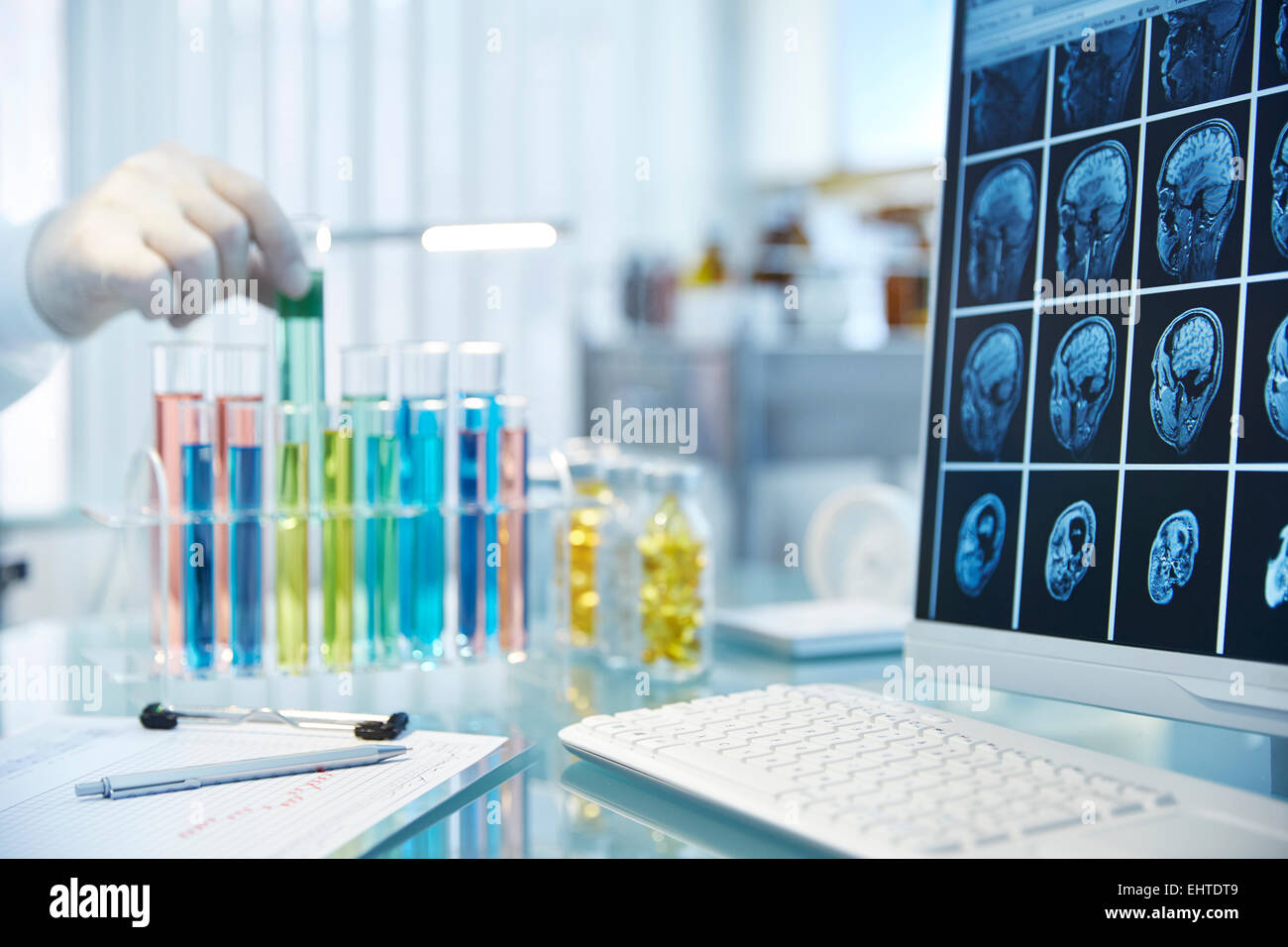 Hand reaching for vial with green fluid,monitor with x-rays in foreground - Stock Image