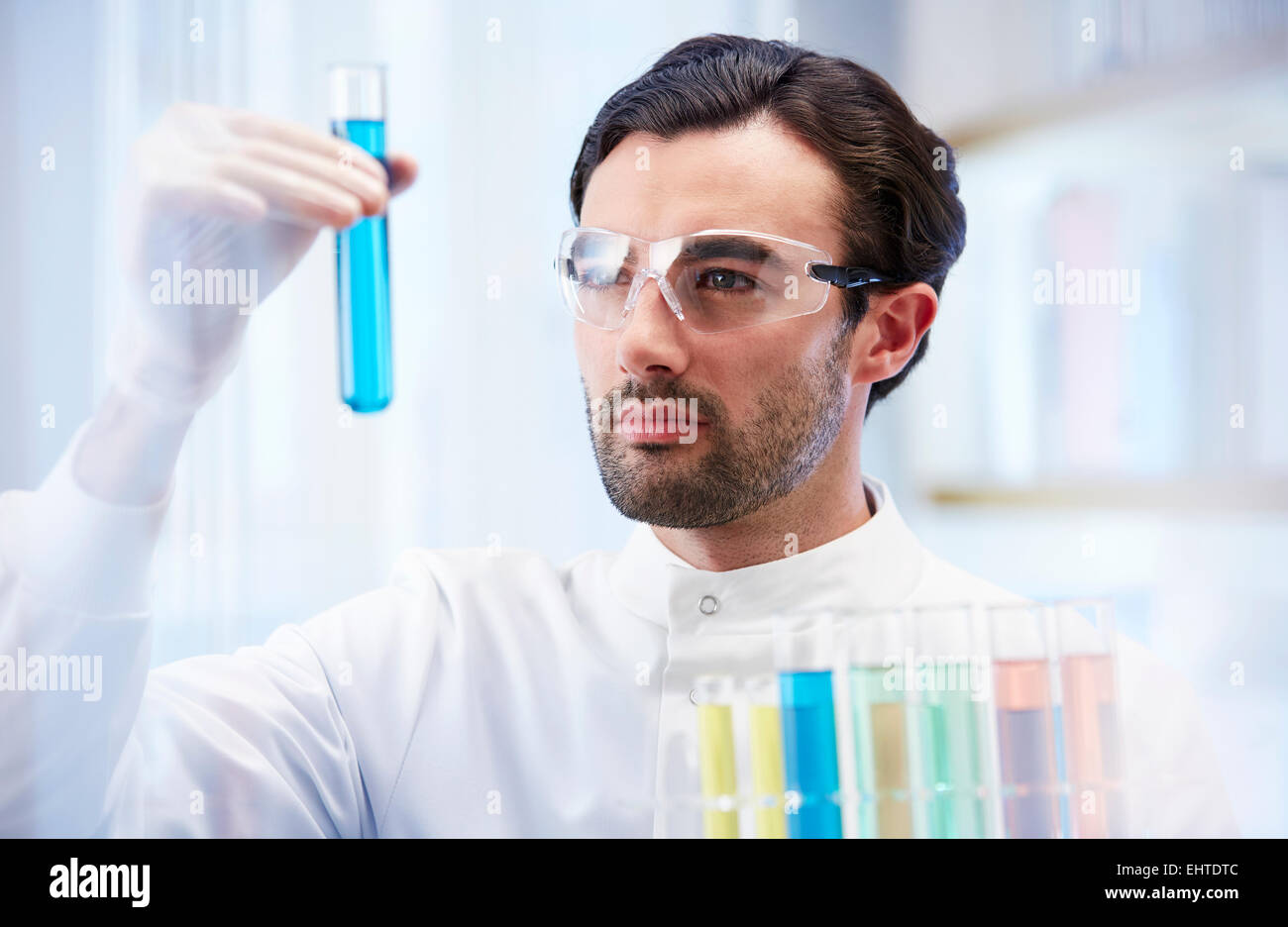 Man in laboratory looking at vial with blue fluid - Stock Image