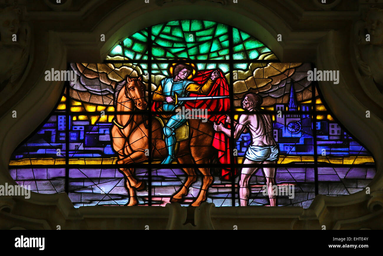 Stained glass window depicting Saint Martin cutting a part of his cloak and handing it over to a beggar, in Martina - Stock Image