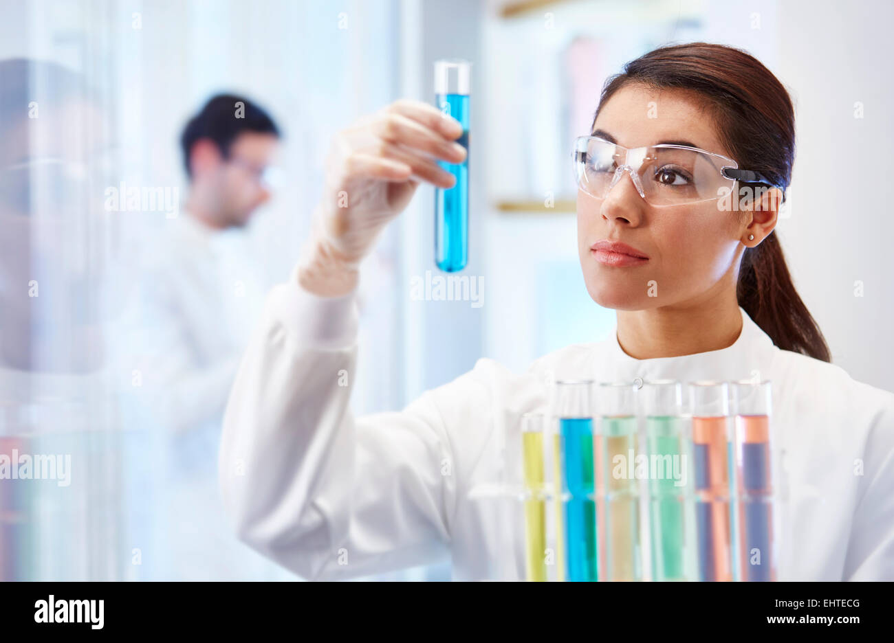 Woman in laboratory looking at vial with blue fluid - Stock Image