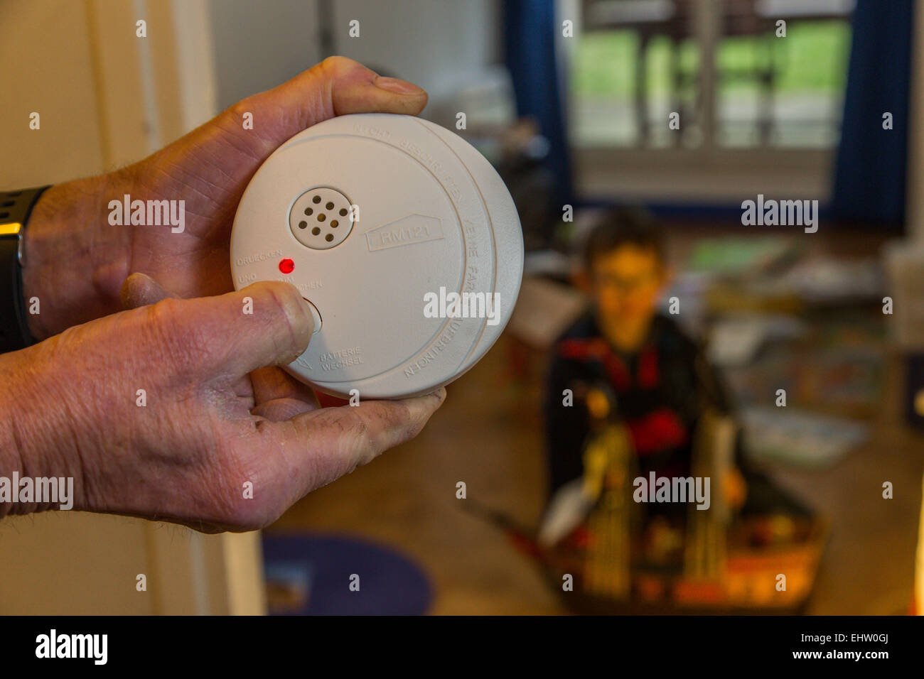 THE INSTALLATION OF A SMOKE DETECTOR TO PREVENT FIRE IN APPARTMENT - Stock Image