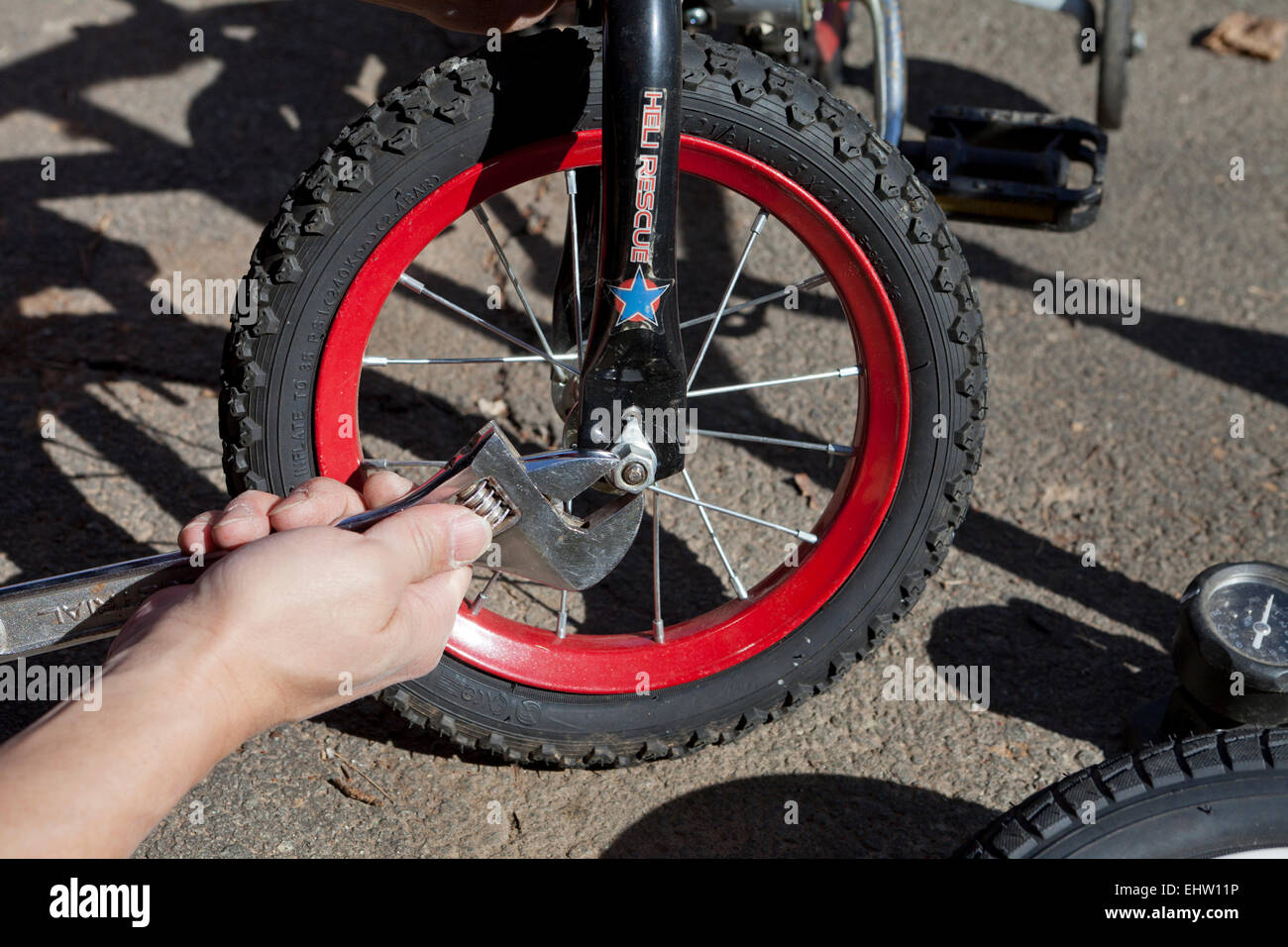 Man removing child's bicycle wheel using crescent wrench - USA - Stock Image