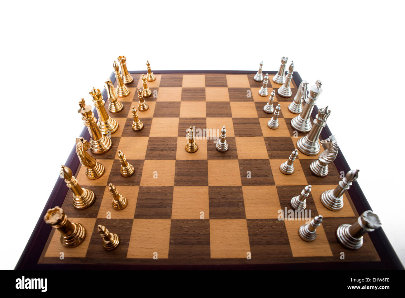 Wooden chess board with gold and silver pieces. - Stock Image