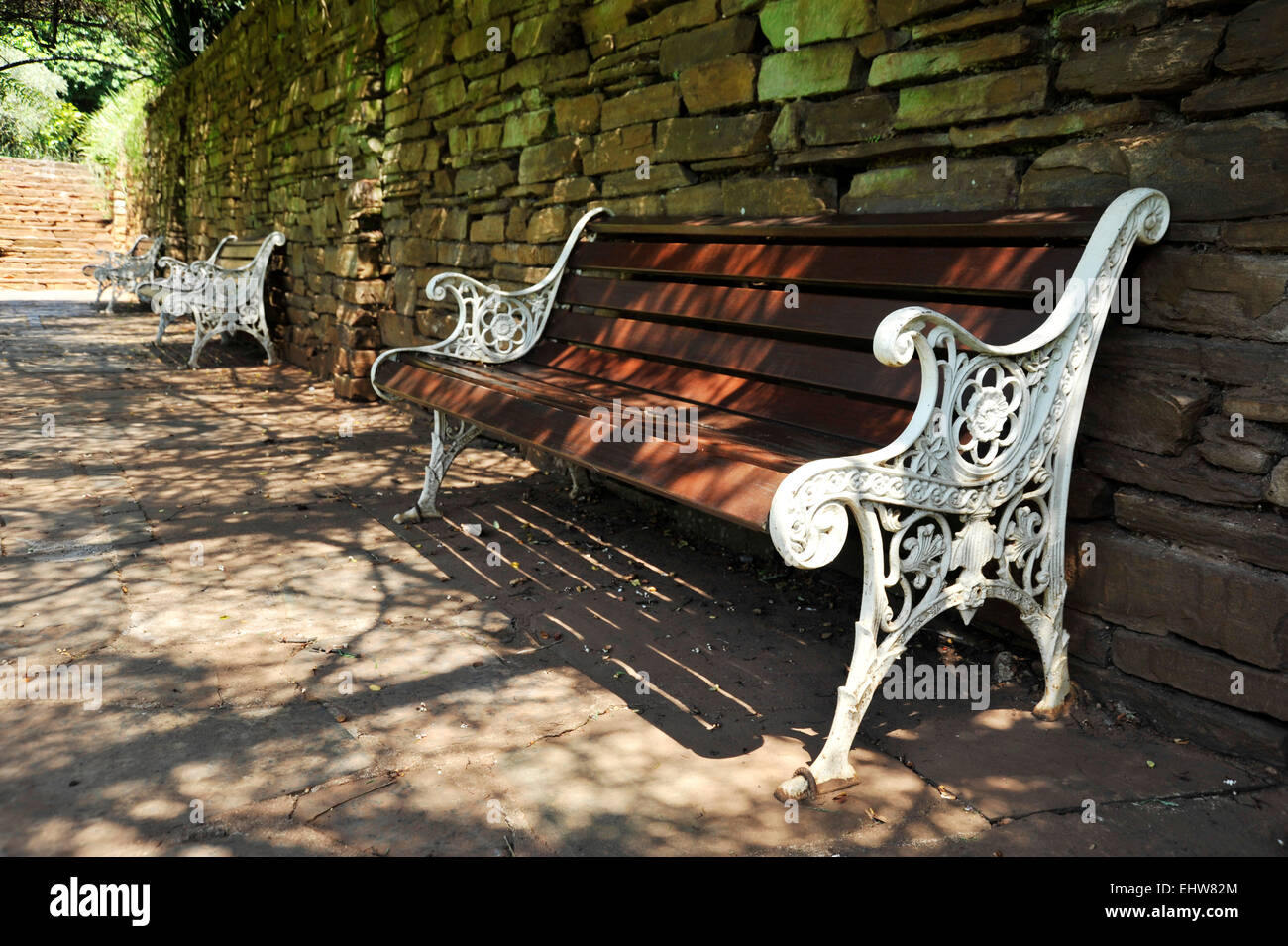 Row Of Outdoor Cast Iron And Wood Benches Next To Weathered Stone