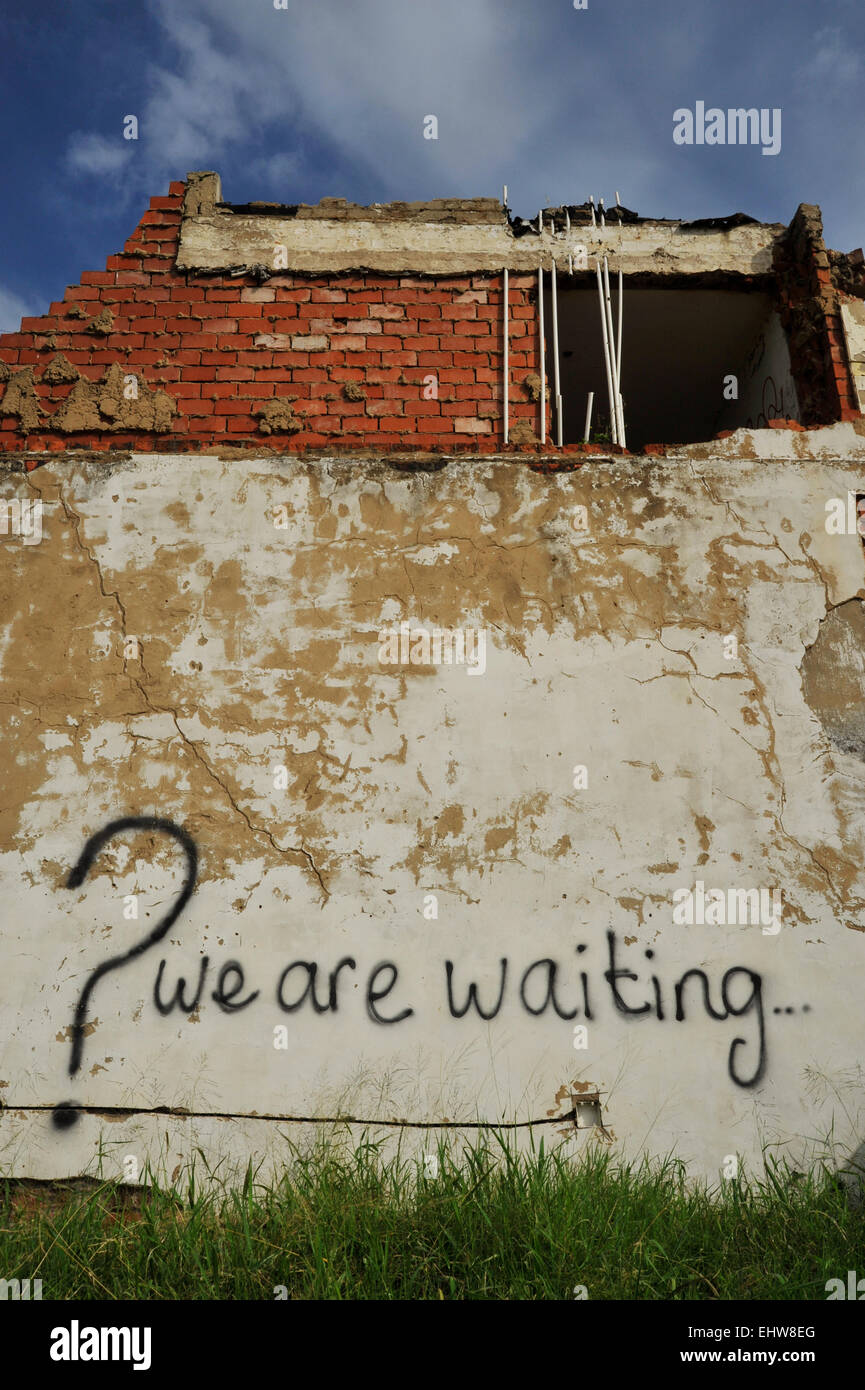 Decaying partly demolished building with 'Why are we waiting' graffiti painted on weathered wall Question - Stock Image