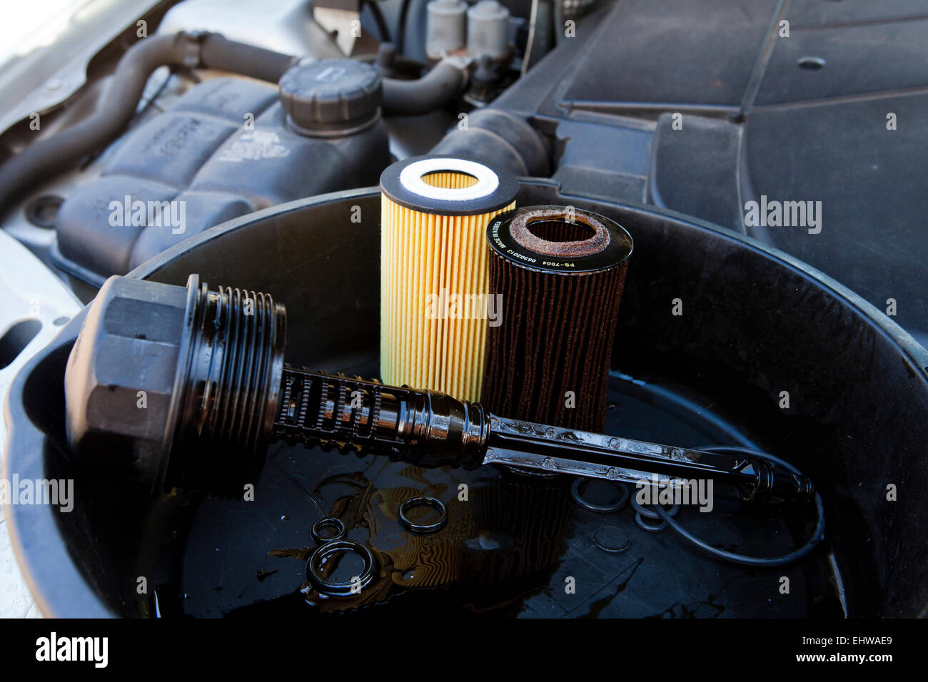 New and used motor oil filters in oil pan - USA - Stock Image