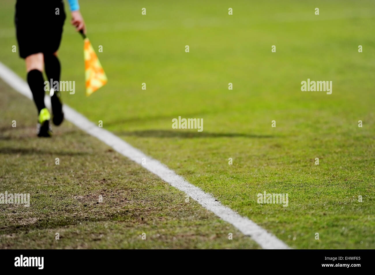 Assistant referees running along the sideline during a soccer match - Stock Image