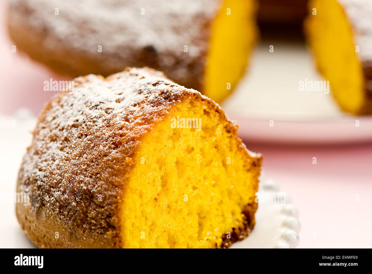 Close up view showing the texture of a slice of freshly baked ring cake on a plate with the cake behind - Stock Image
