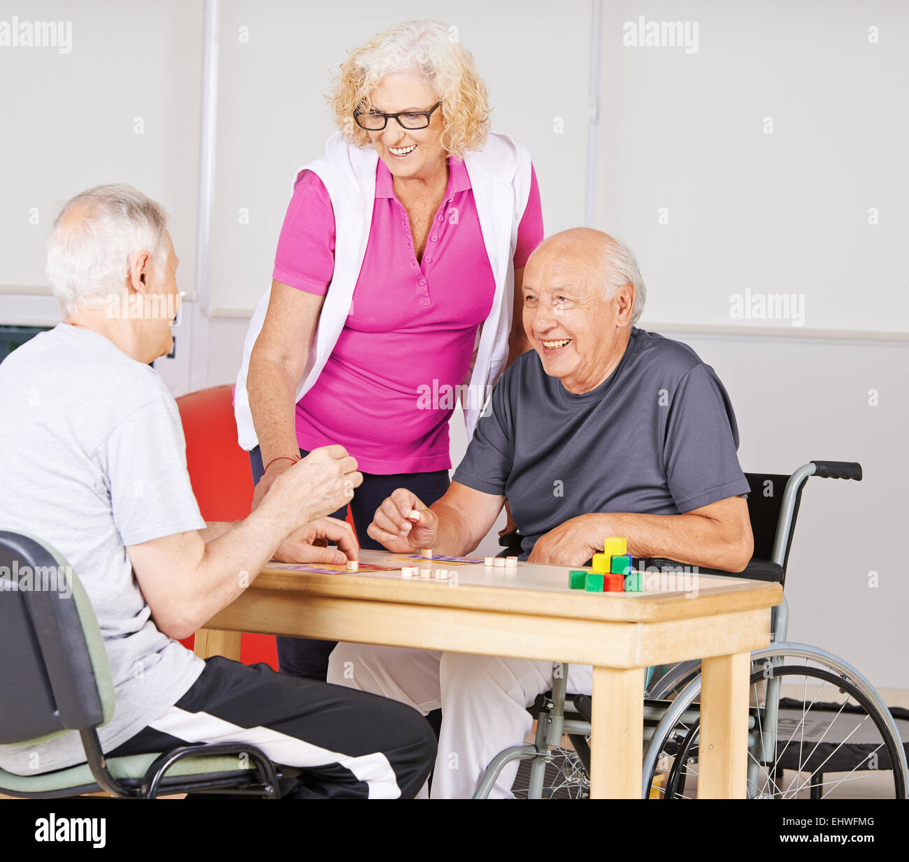 Happy senior people playing Bingo together in a nursing home - Stock Image