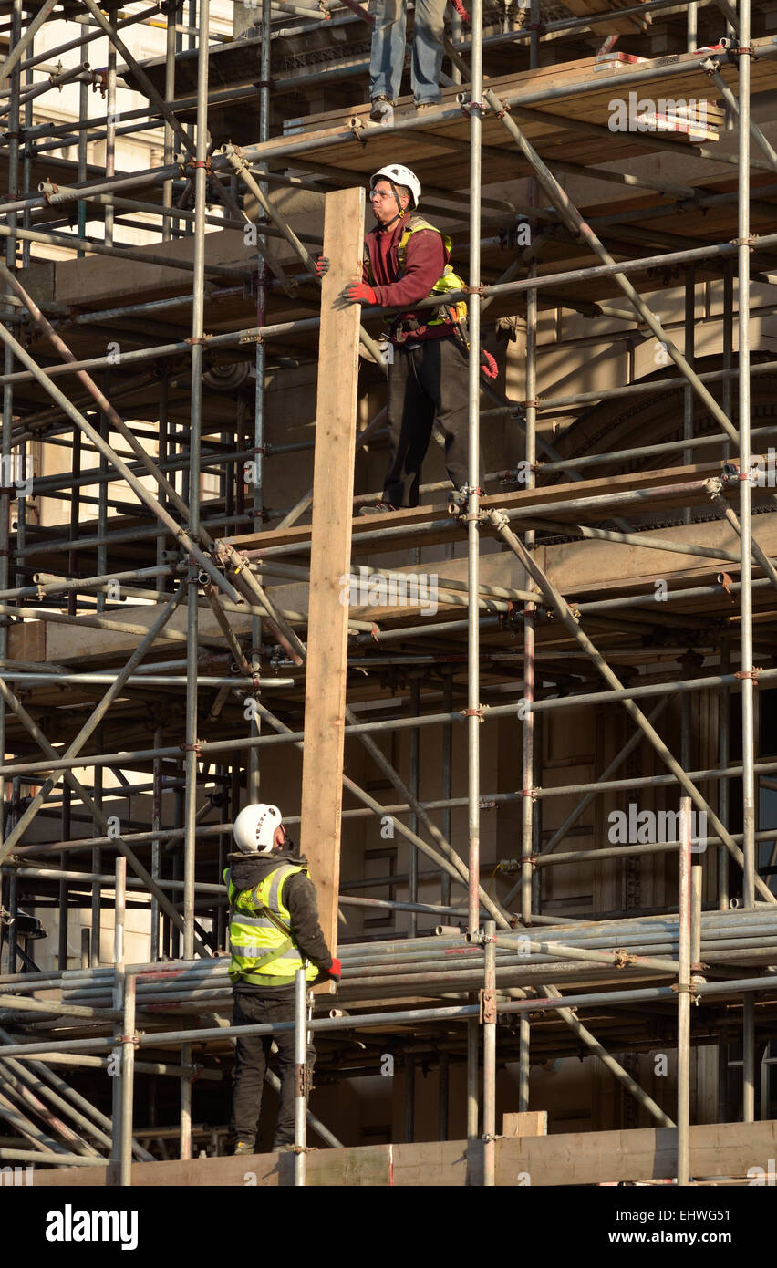 London, England, UK. Construction workers passing long planks up scaffolding - Stock Image