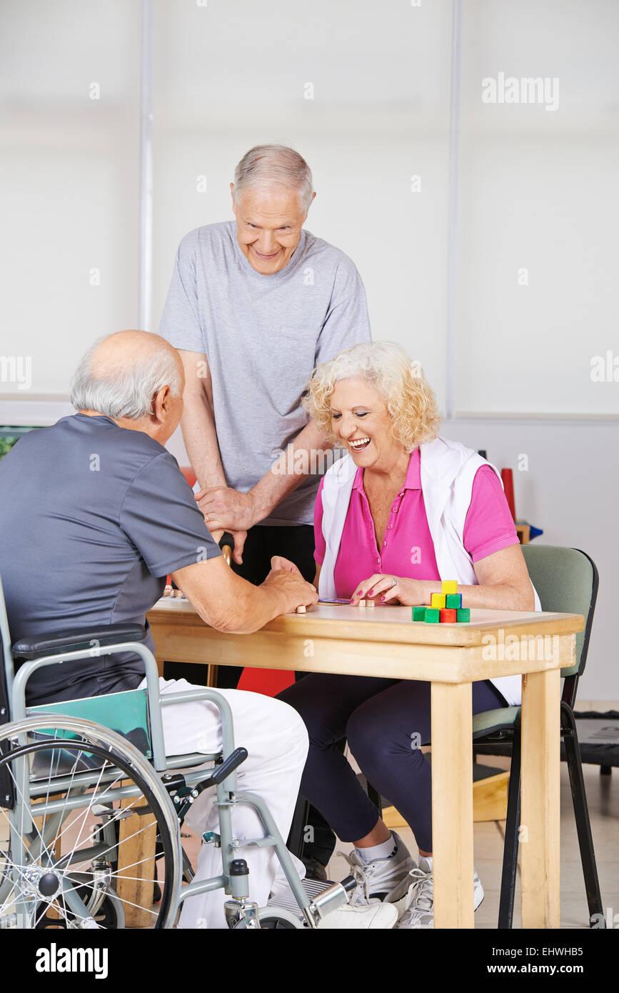 Happy senior people during rehab playing Bingo together - Stock Image