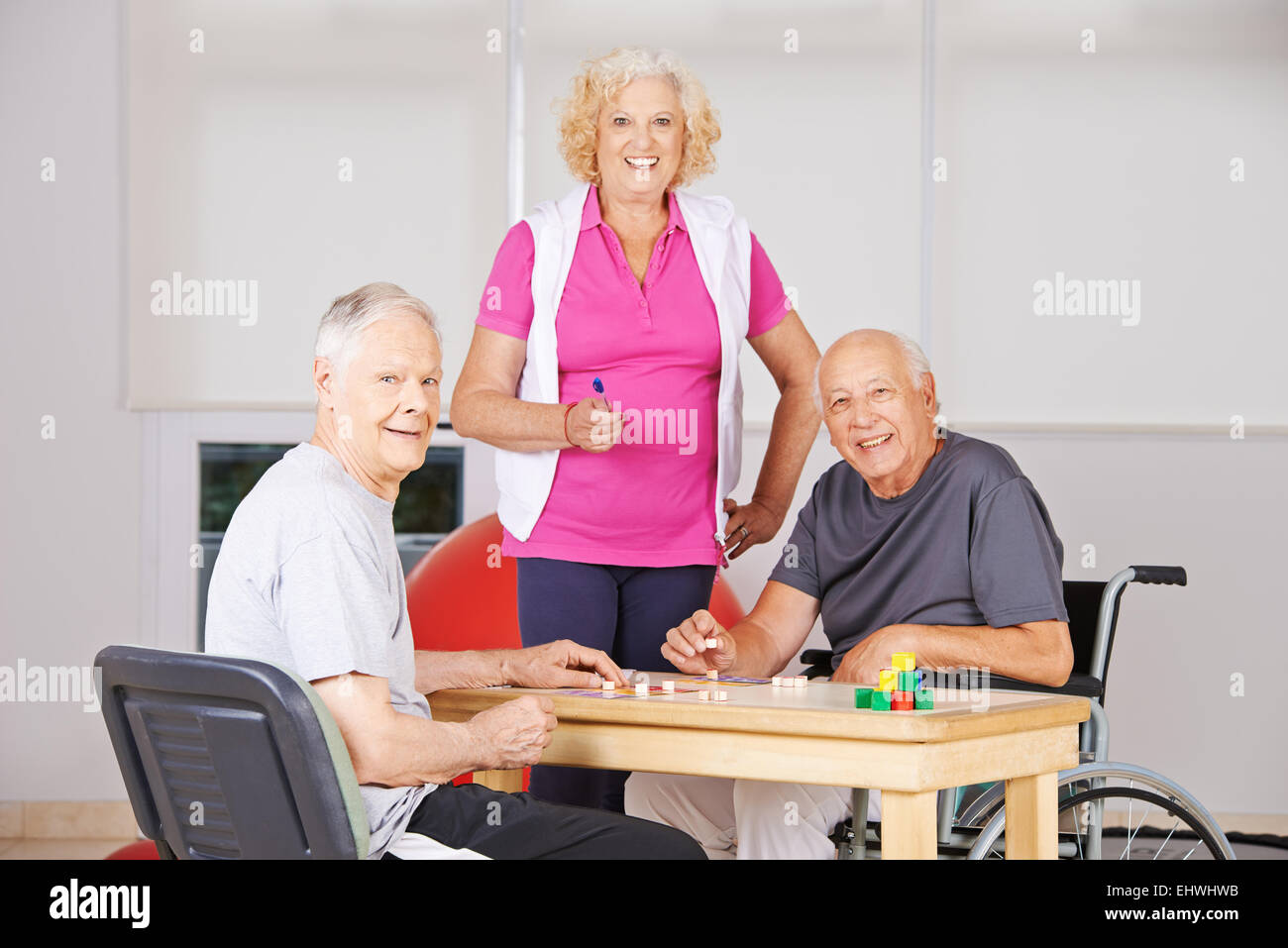 Three happy senior citizens playing Bingo together in a nursing home - Stock Image