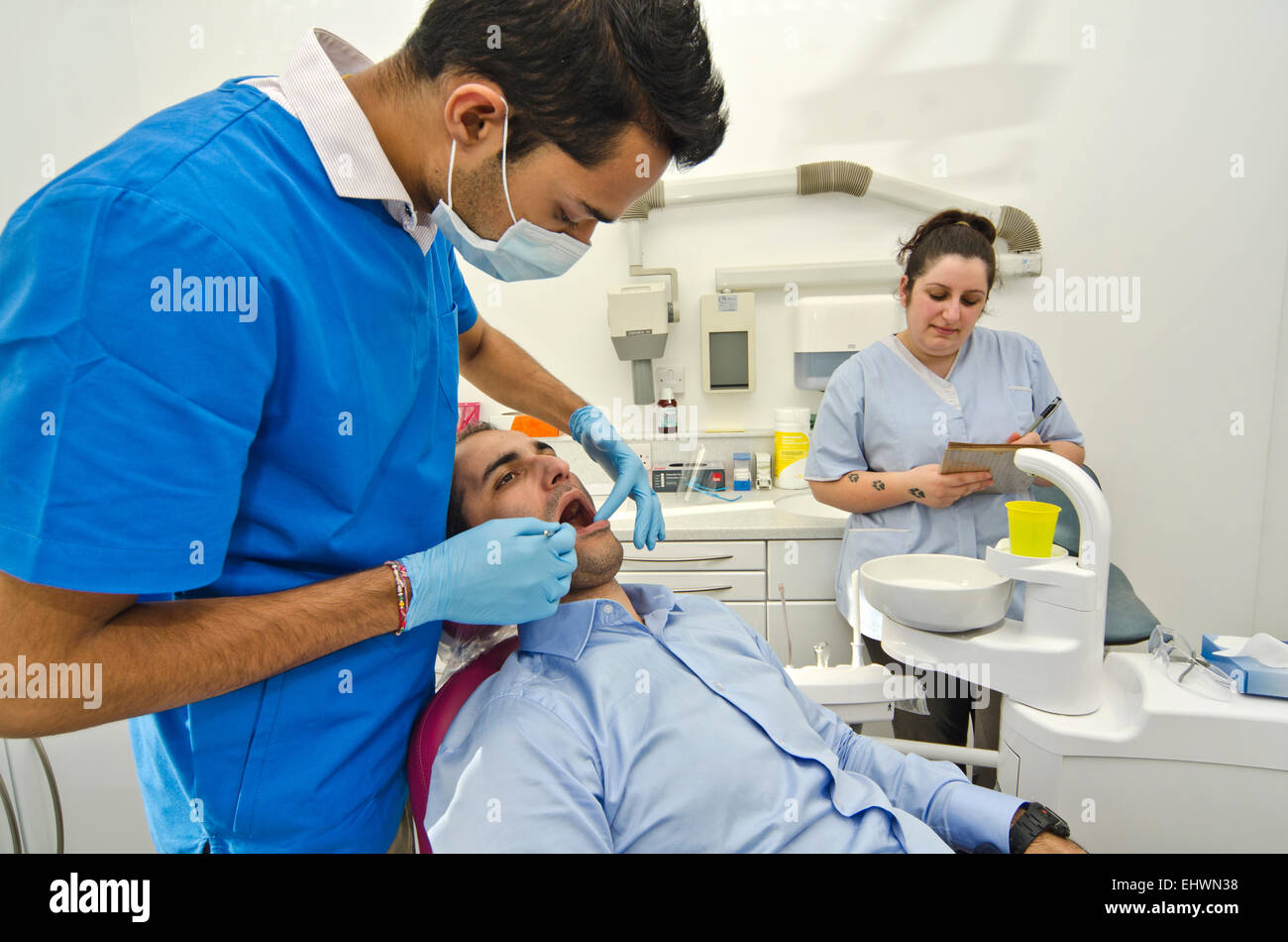 DENTIST EXAMINE  MALE PATIENT MOUTH WITH GREAT CONCENTRATION, WHILE NURSE TAKING NOTES - Stock Image