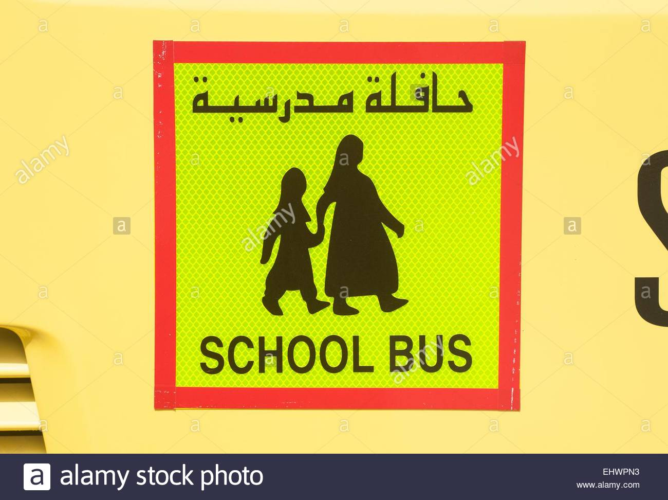 Dubai UAE School bus sign in English and arabic with figures wearing typical Islamic dress. - Stock Image