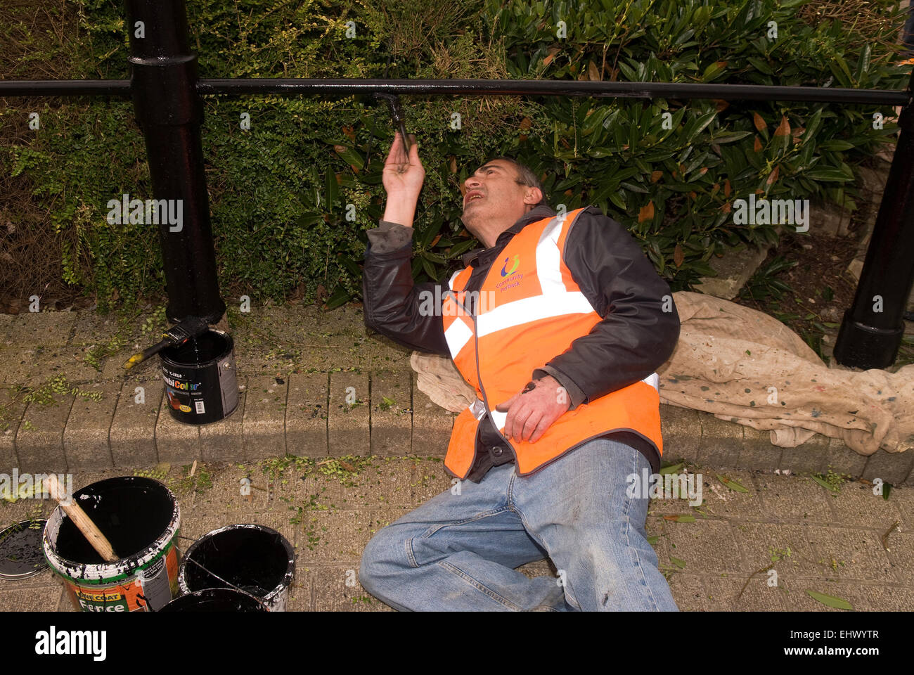 Convicted offender undertaking Community Payback task painting railings, Petersfield, Hampshire, UK. - Stock Image