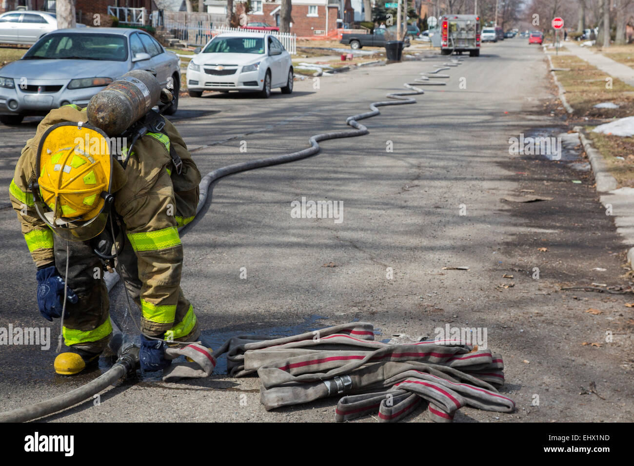 Detroit, Michigan - A firefighters connects hoses while fighting a fire which destroyed a vacant home in Detroit. - Stock Image