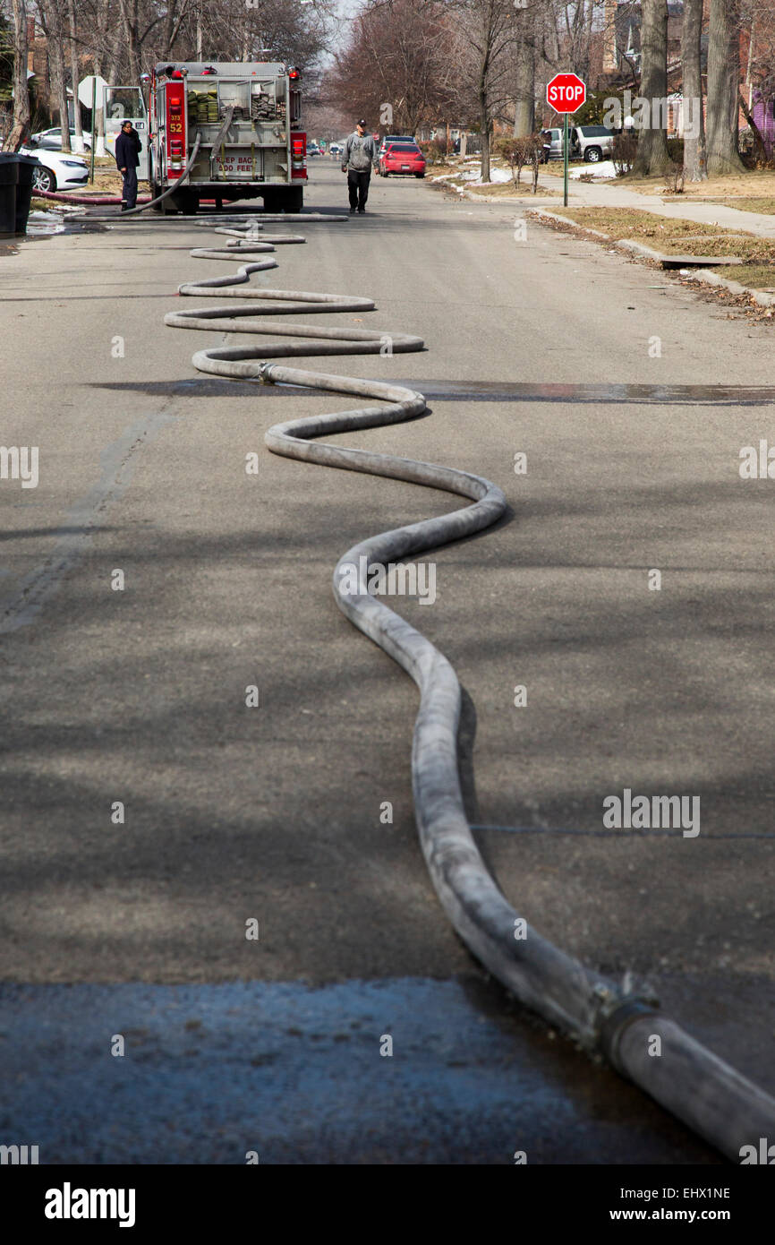 Detroit, Michigan - Fire hose lays in the street as firefighters battle a fire which destroyed a vacant home in - Stock Image