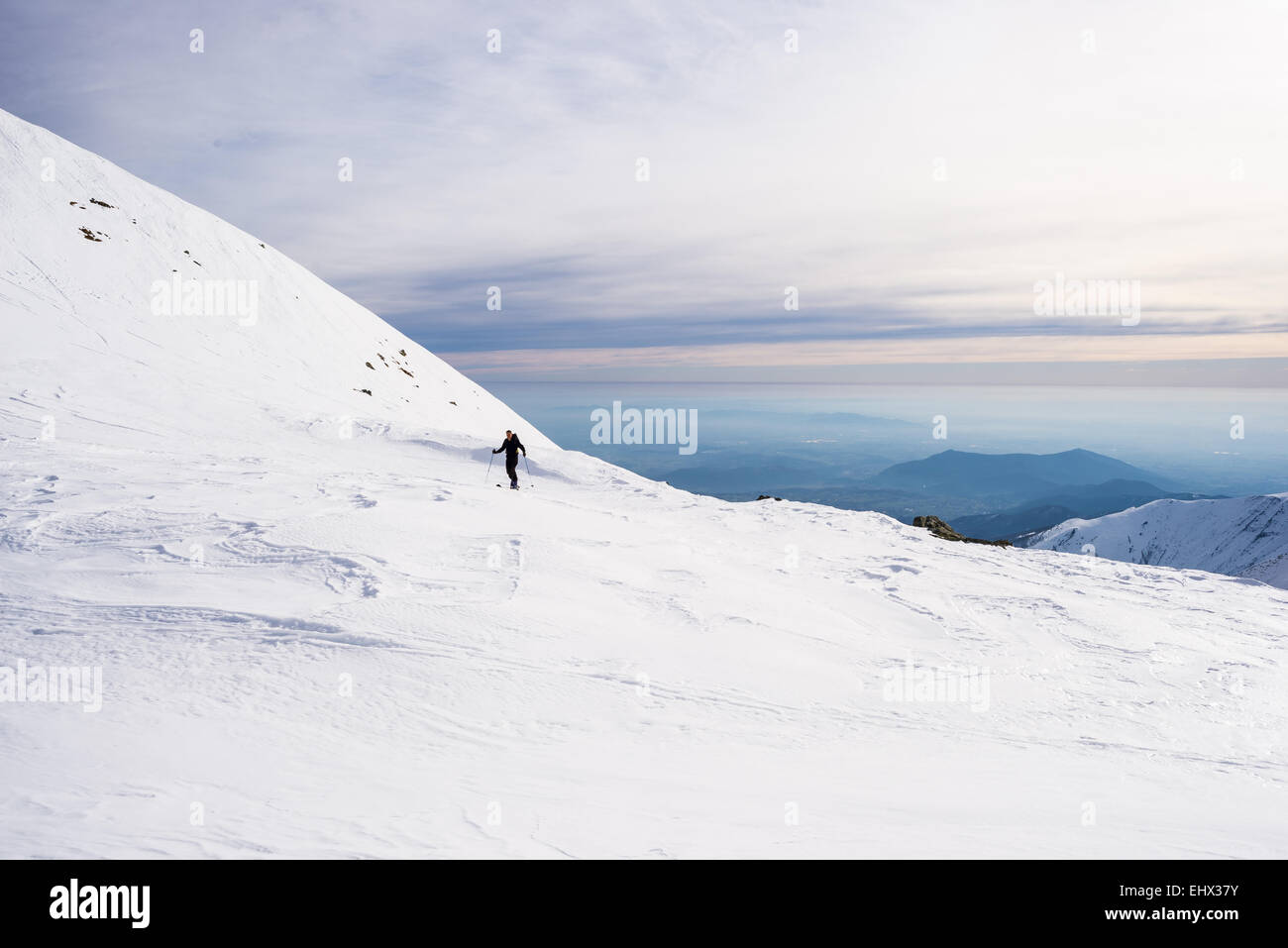 Back country skier hiking uphill on snowy slope with scenic view in the background. Concept of conquering adversities. - Stock Image