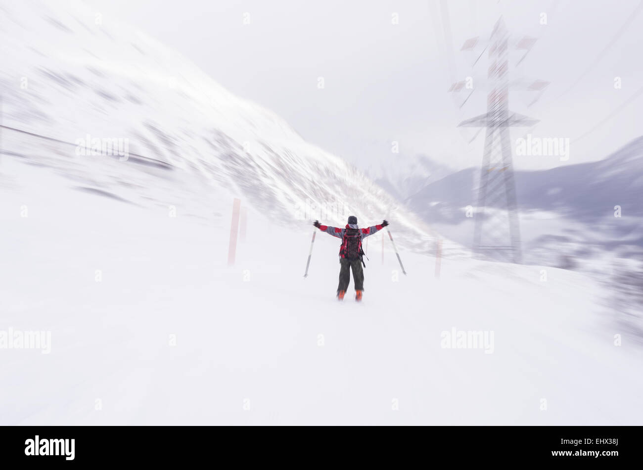 Speed skiing on snowy slope in the famous and scenic ski resort of La Thuile, Aosta Valley, Italy. Cloudy sky, snowing. - Stock Image