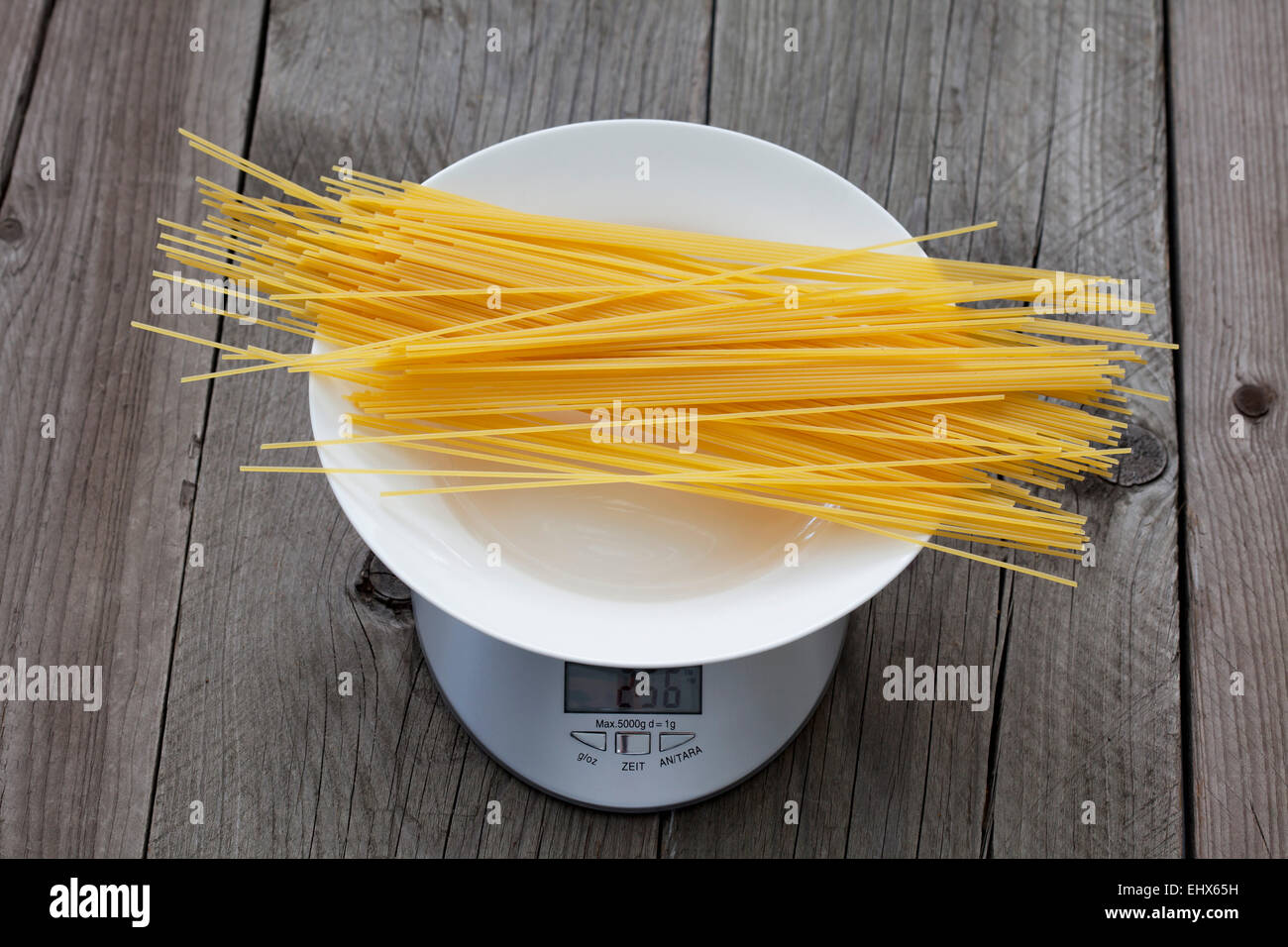 Row spaghetti on plate and scale on wood - Stock Image